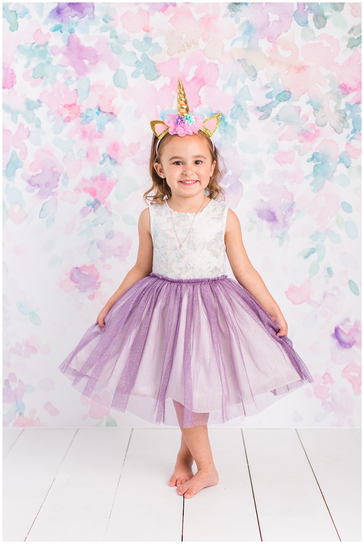 4 year old Sadie curtsey wearing a white and purple sparkling dress and unicorn headband.