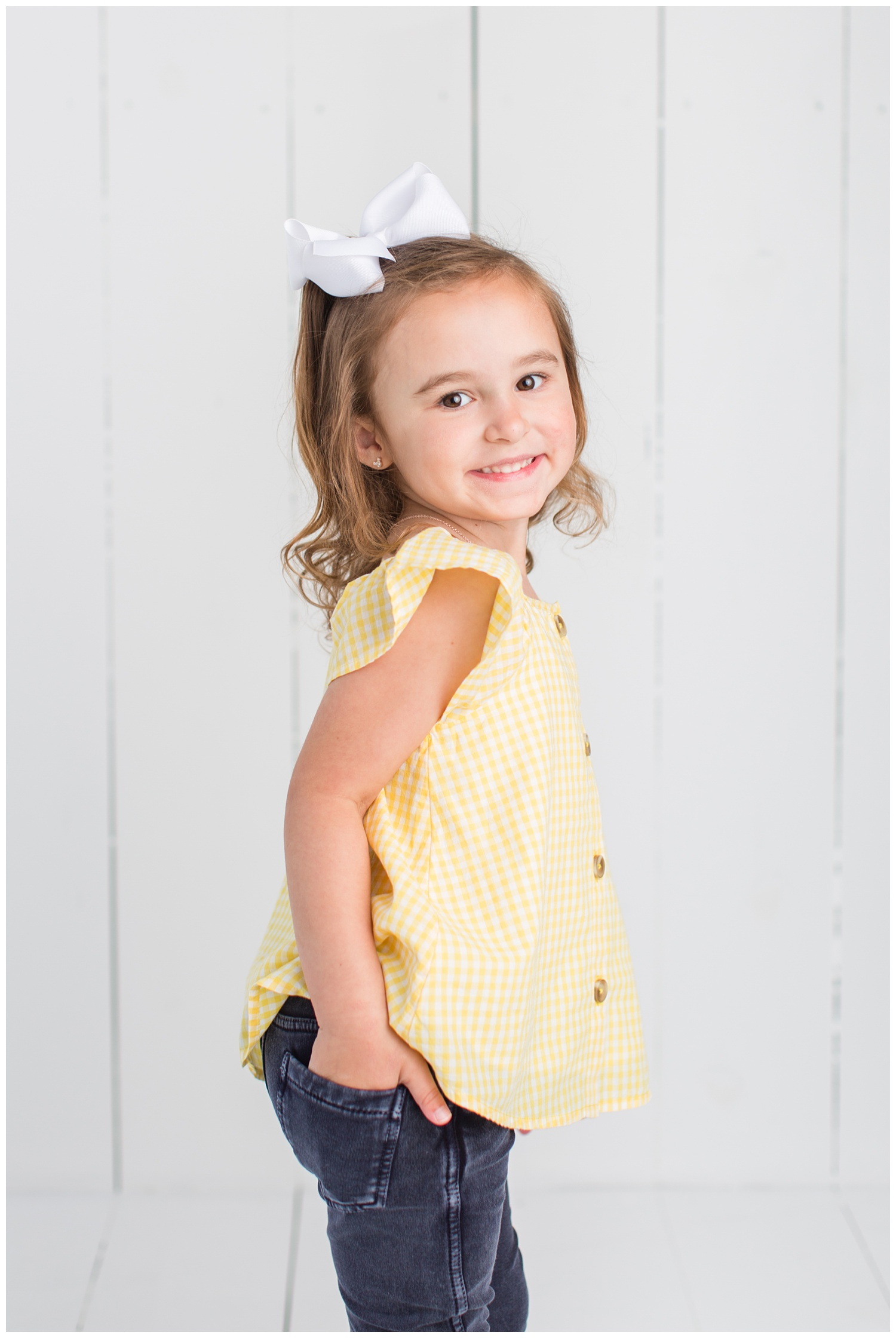 4 Year old Sadie wearing a yellow gingham top posing with her hand in her back pocket on a white wood background.