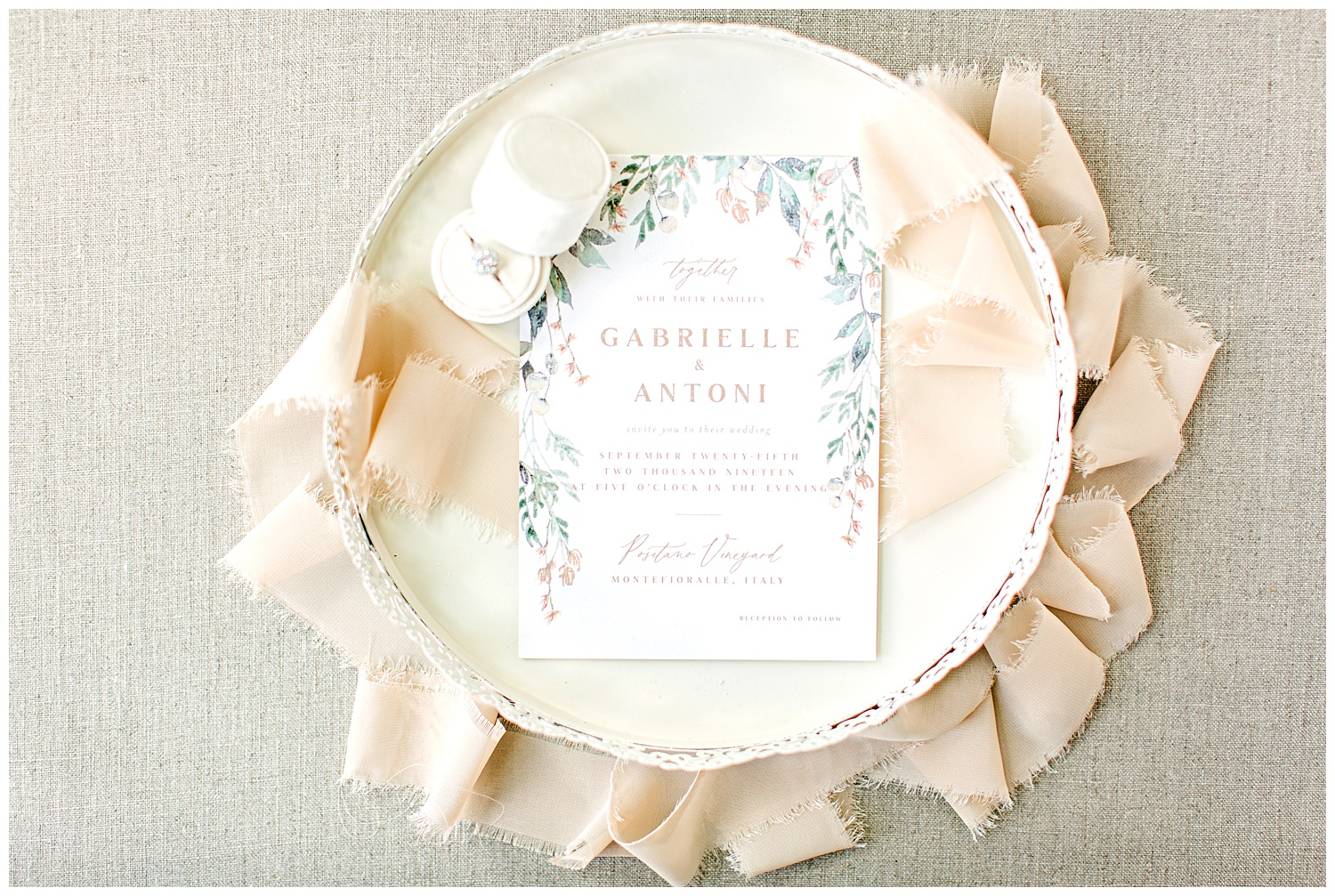 Peach, green and dusty blue watercolor floral wedding invitation from Elli beautifully styled on a cream decorative tray with a cream ring box and peach frayed edge ribbon.