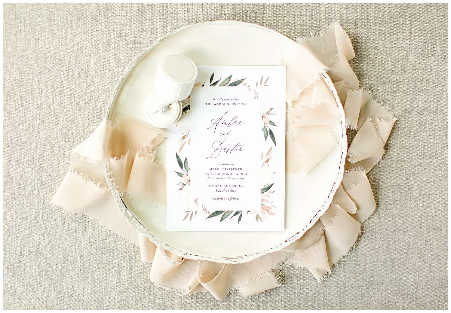 Peach and green watercolor floral wedding invitation from Elli beautifully styled on a cream decorative tray with a cream ring box and peach frayed edge ribbon.
