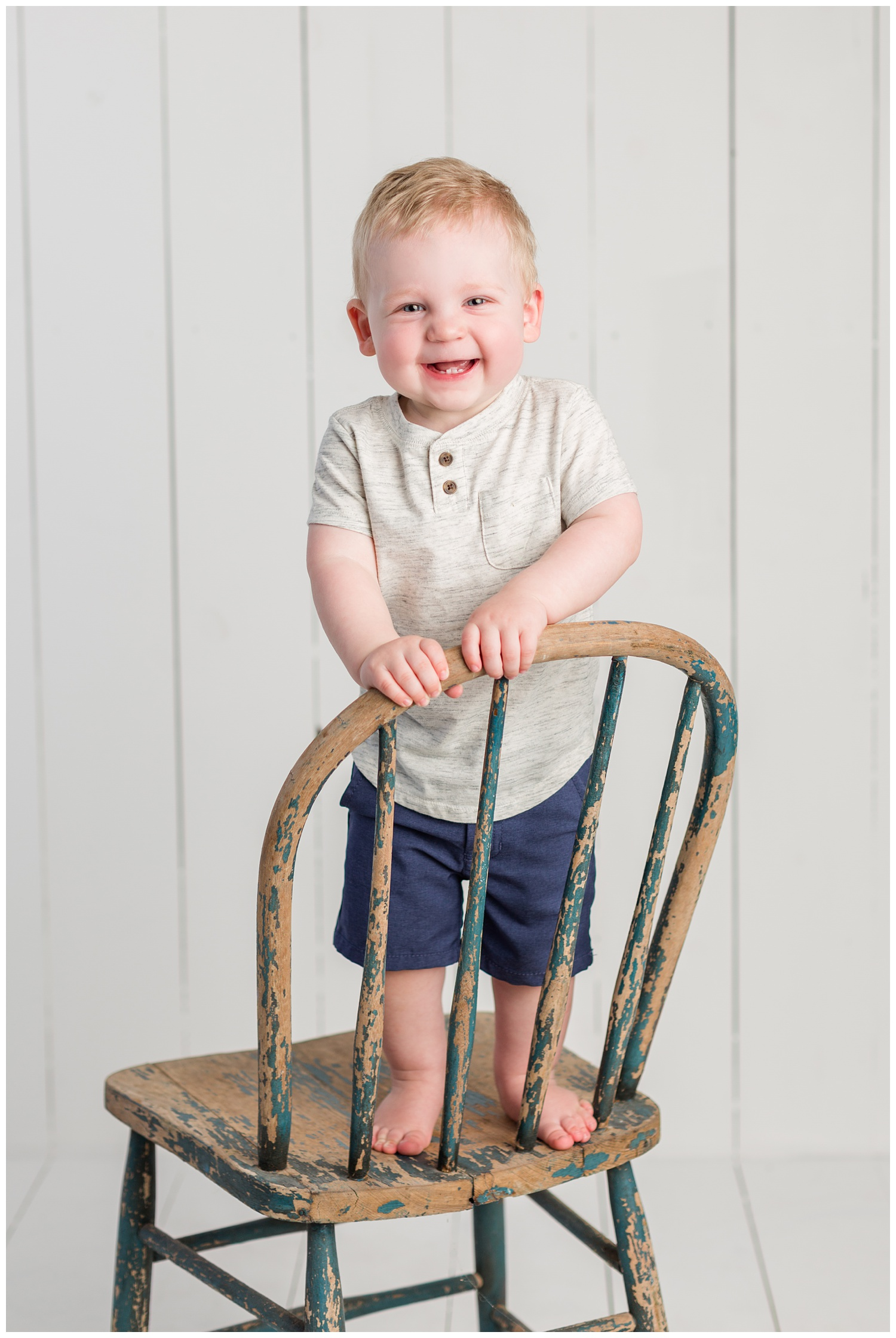 Baby Carter standing on a rustic navy chair wearing a heather gray shirt and navy shorts smiling for his first birthday photo | CB Studio