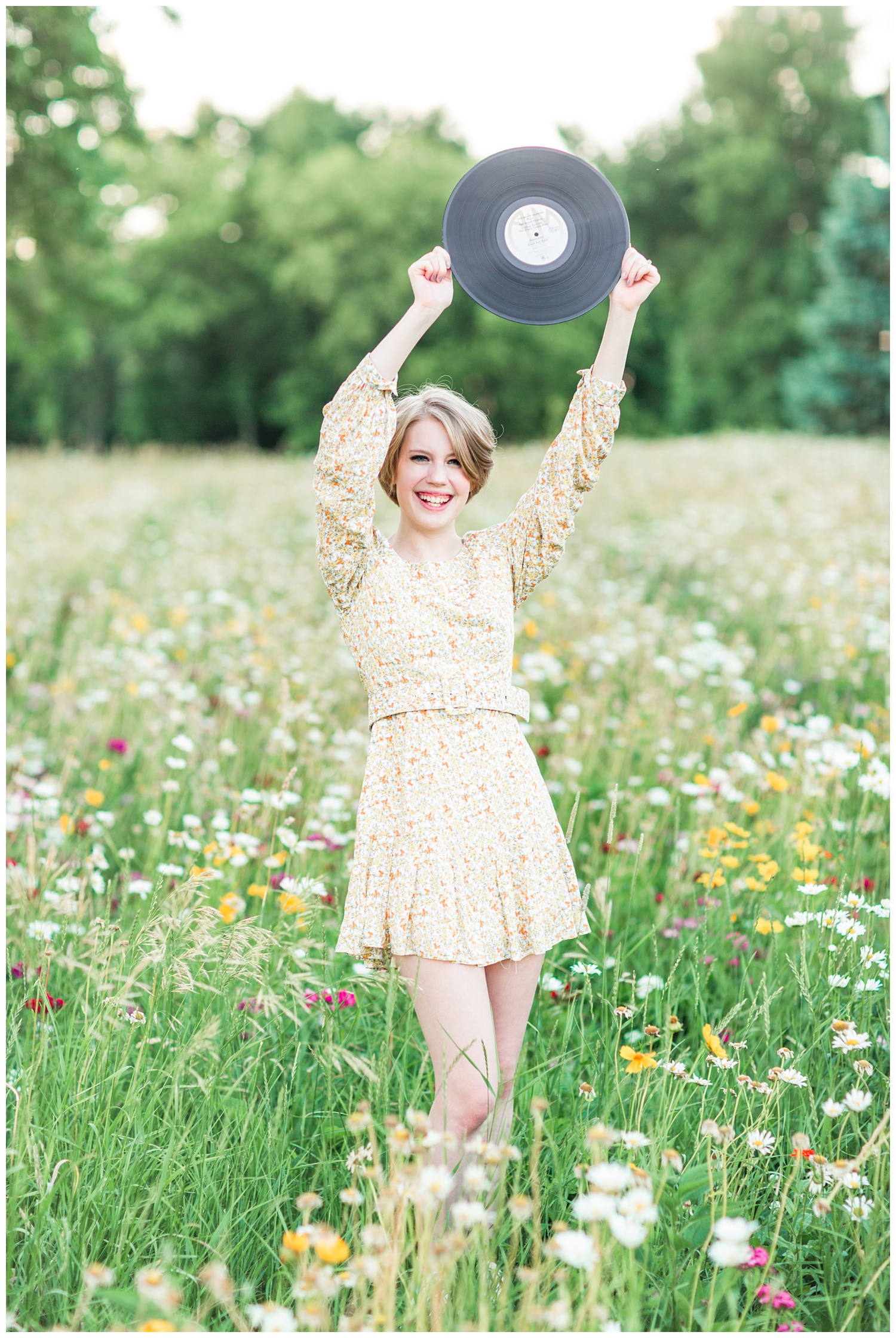 Vintage, film inspired, 70s retro styled senior holding a vinyl record in a flower field. | CB Studio