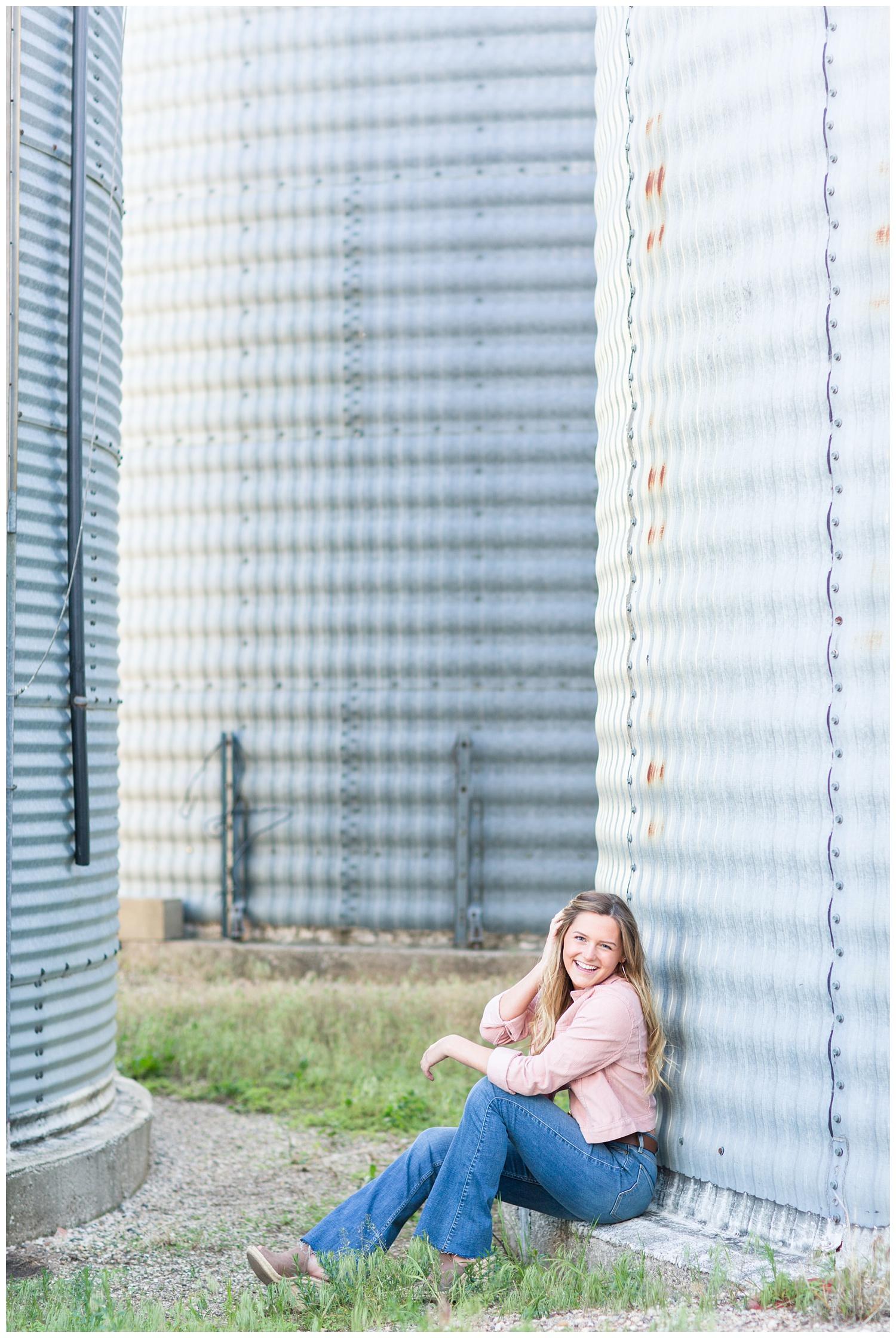 Senior girl sitting next to a grain bin in rural north central Iowa | CB Studio