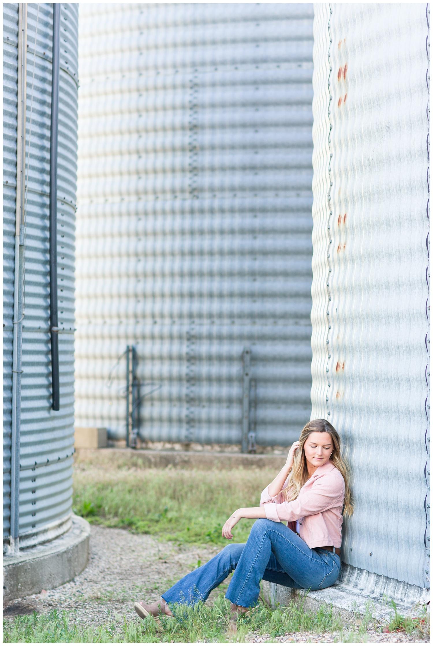 Senior girl sits next to a grain bin in rural north central Iowa | CB Studio