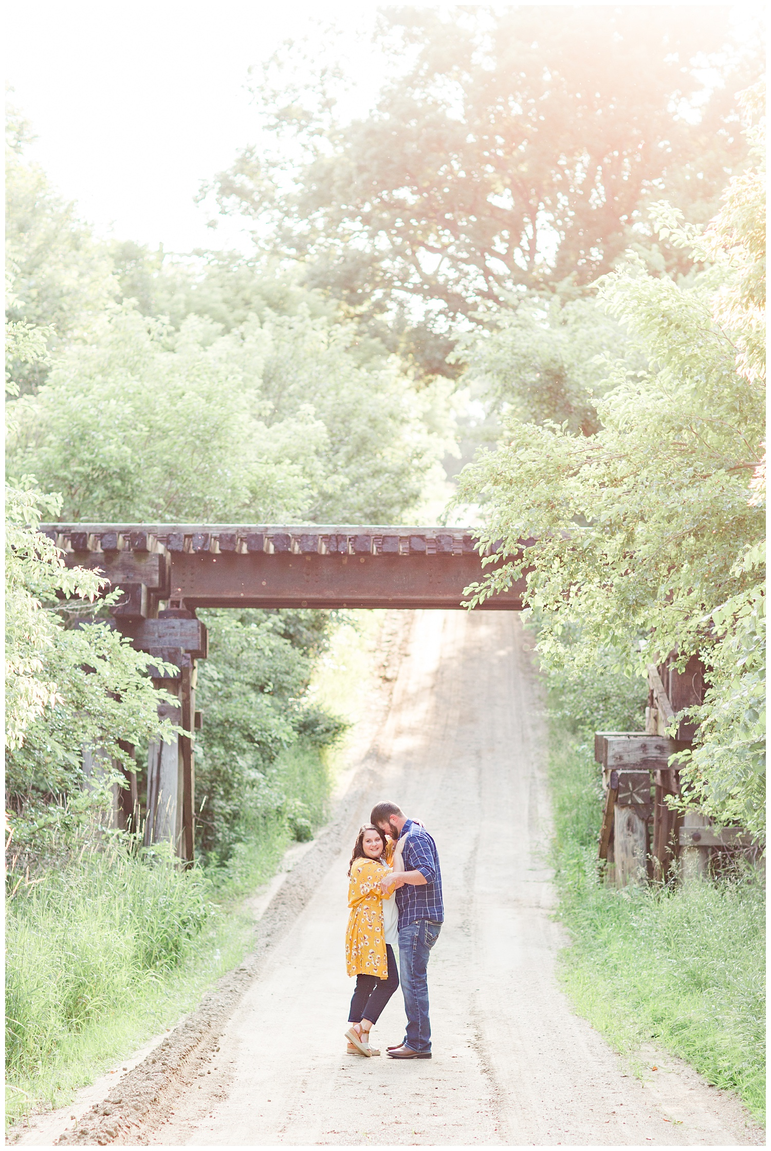 Engaged couple stands under a train trestle bridge on a farm in north central Iowa | CB Studio