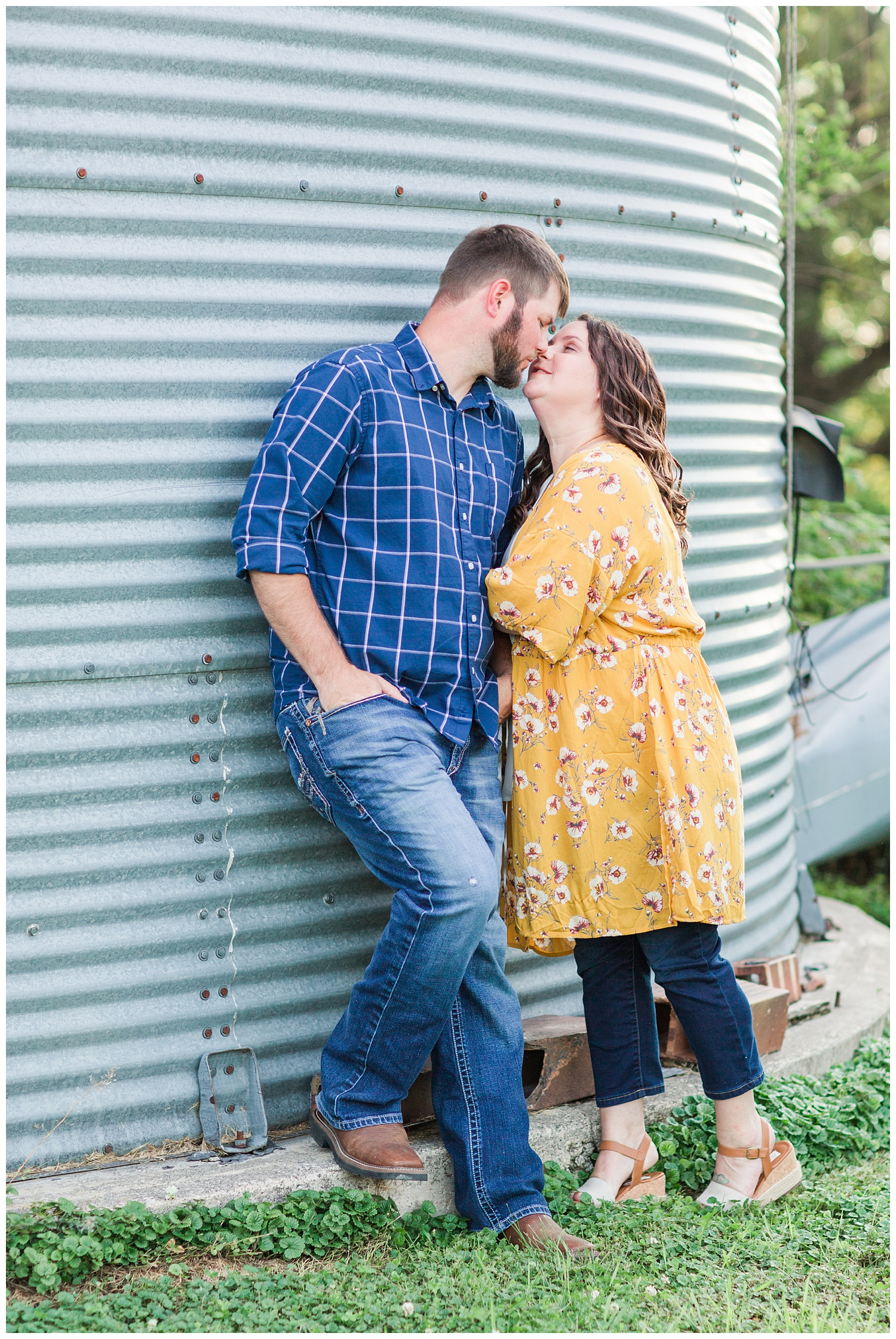 Engaged couple kiss next to a grain bin on a farm in north central Iowa | CB Studio