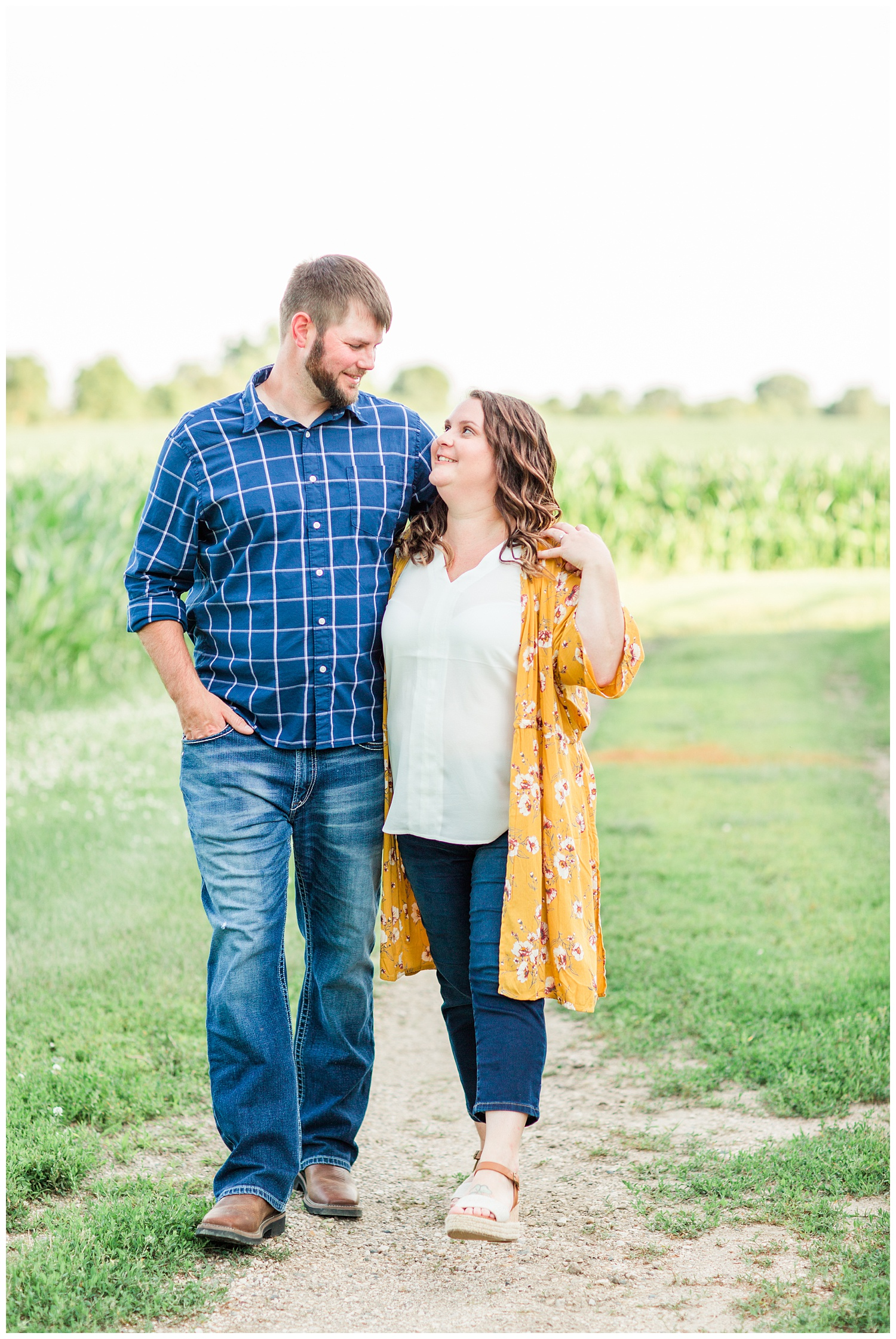 Engaged couple walks along a corn field on a farm in north central Iowa | CB Studio