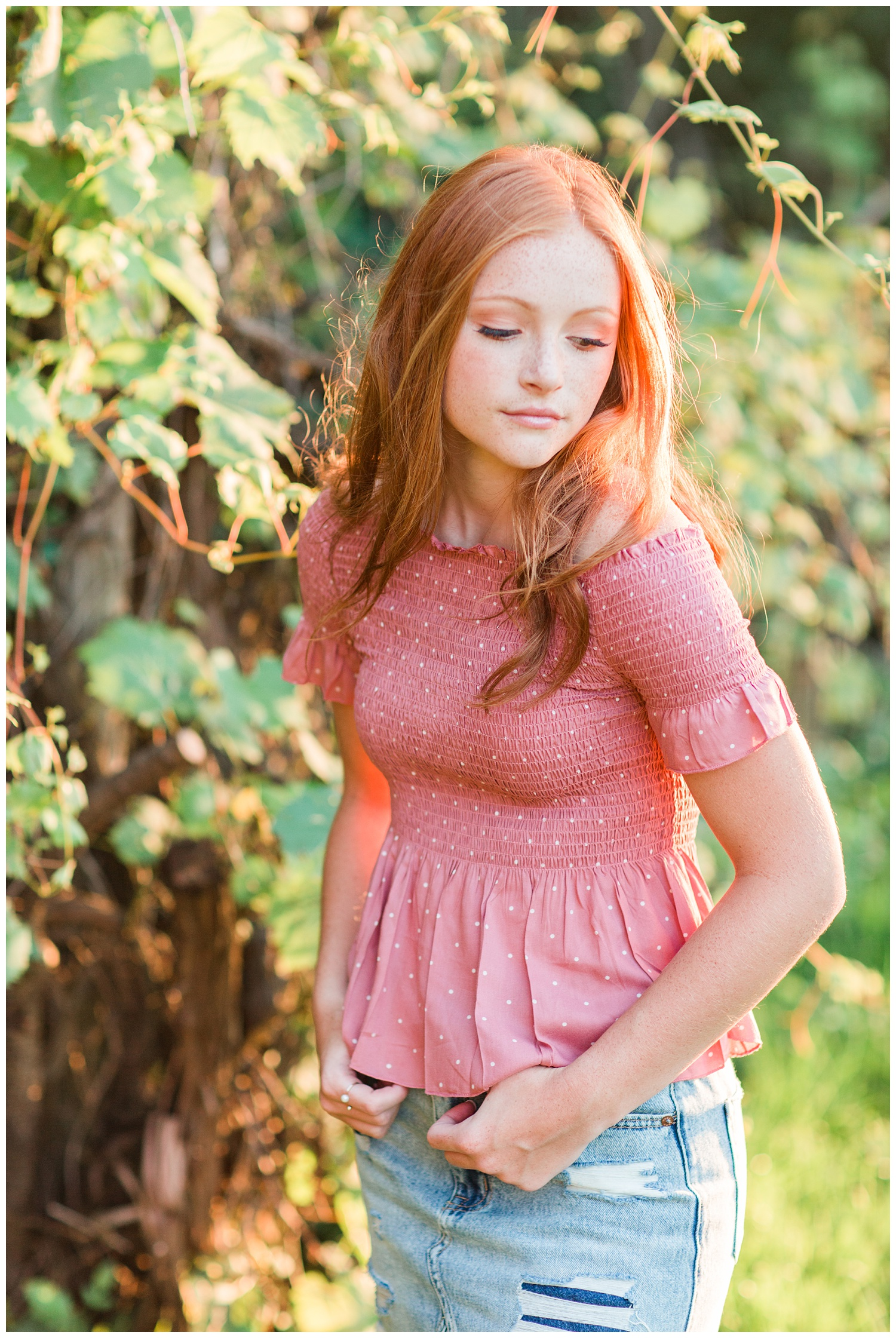 Senior girl wearing a pink, smocked, off the should top looking over her shoulder during golden hour in West Bend, Iowa | CB Studio
