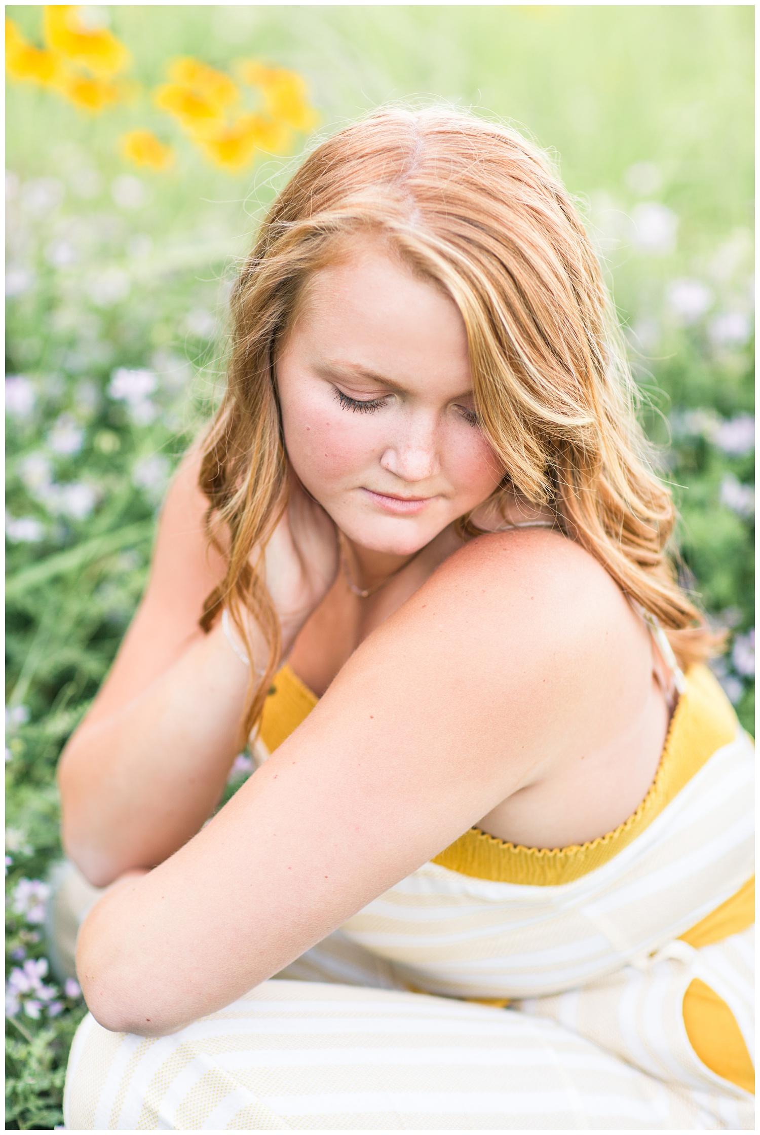 Senior girl wearing a cream and mustard jumpsuit sitting in a flower field at Smith Lake, Algona, Iowa | CB Studio