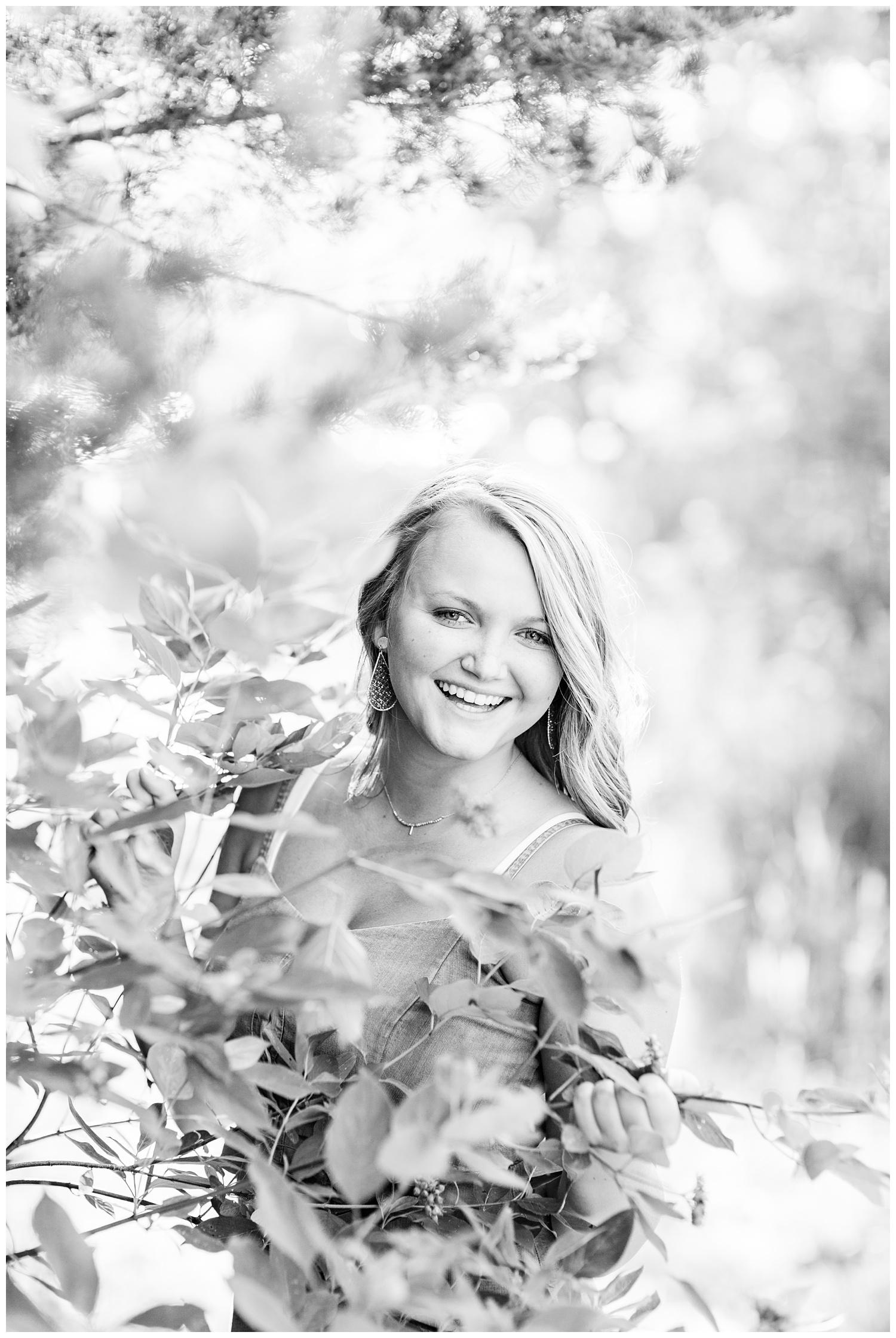 Senior girl wearing laughing behind a tree branch at Smith Lake, Algona, Iowa | CB Studio