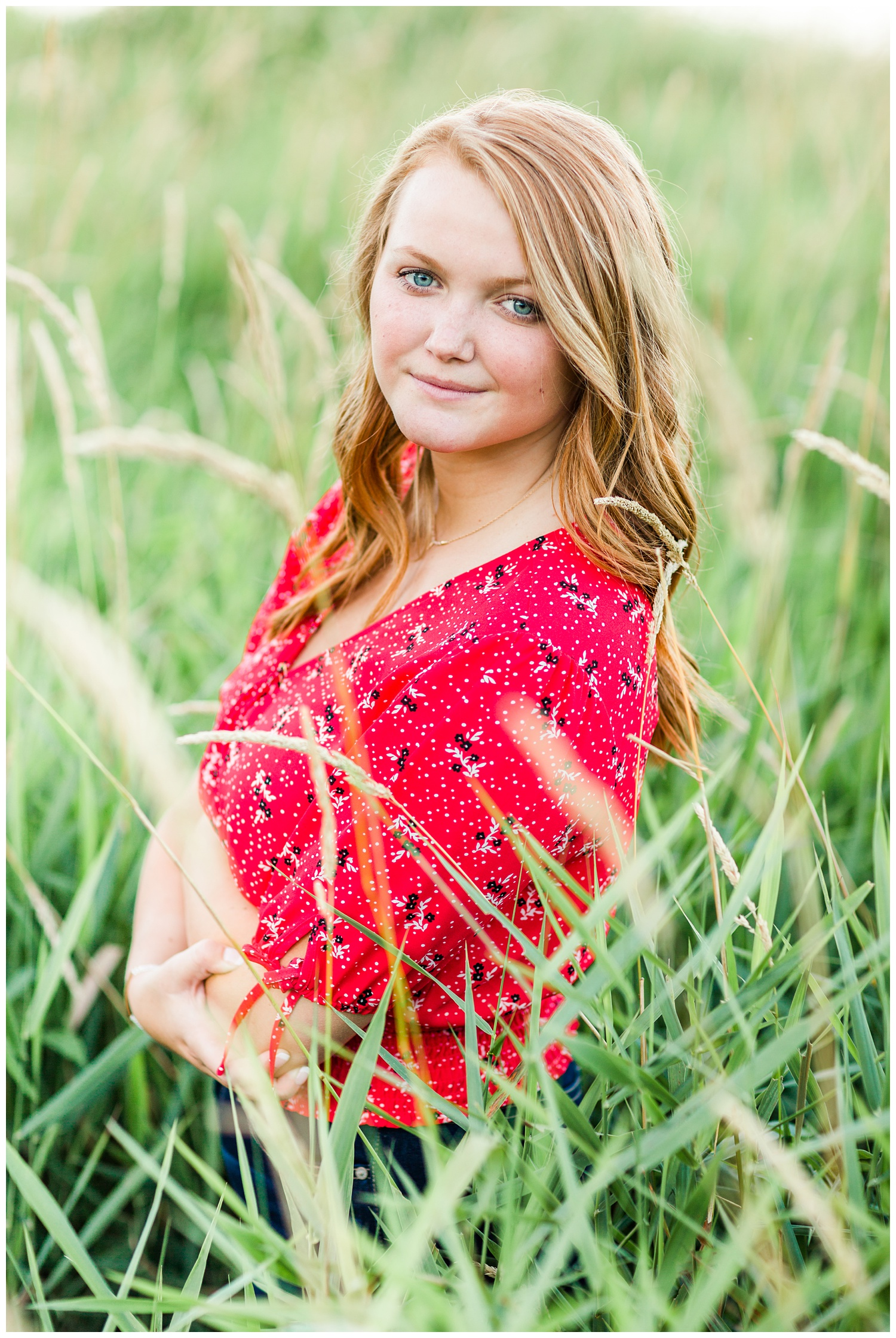 Senior girl wearing a red floral blouse standing in a grassy field at Smith Lake, Algona, Iowa | CB Studio