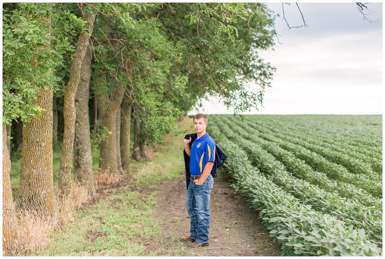 Senior boy wearing an FFA shirt stands next to a bean field holding his FFA jacket on a rural farm in Iowa | CB Studio