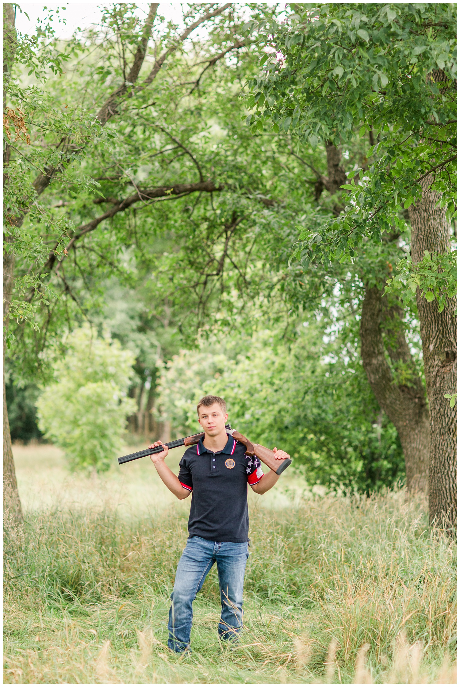 Senior boy wearing trapshooting gear carrying a shotgun around his neck in a grassy field surrounded by trees a on rural Iowa farm | CB Studio