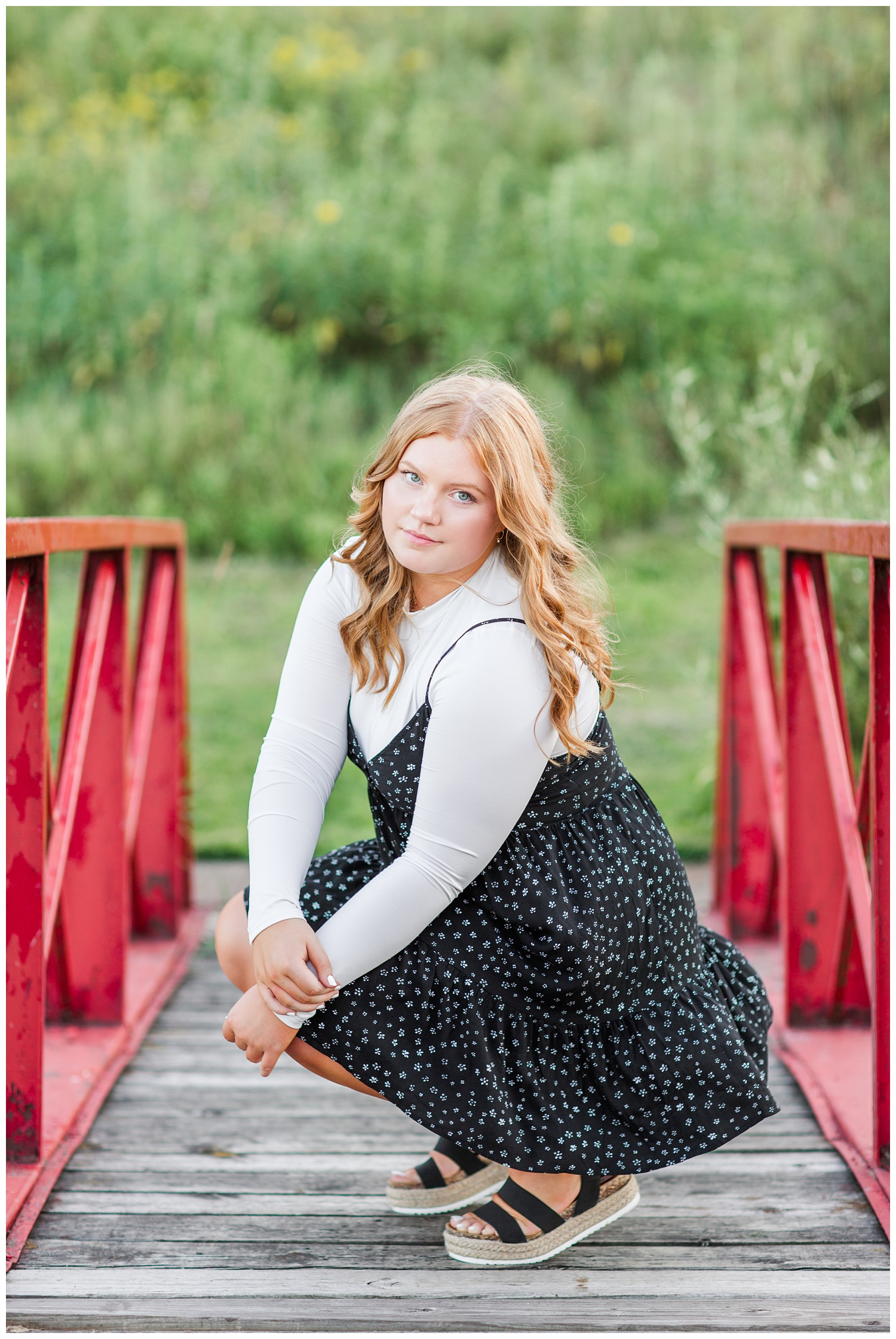 Senior girl wearing a black floral dress sits on a red bridge at Water's Edge Nature Center in Algona, Iowa | CB Studio