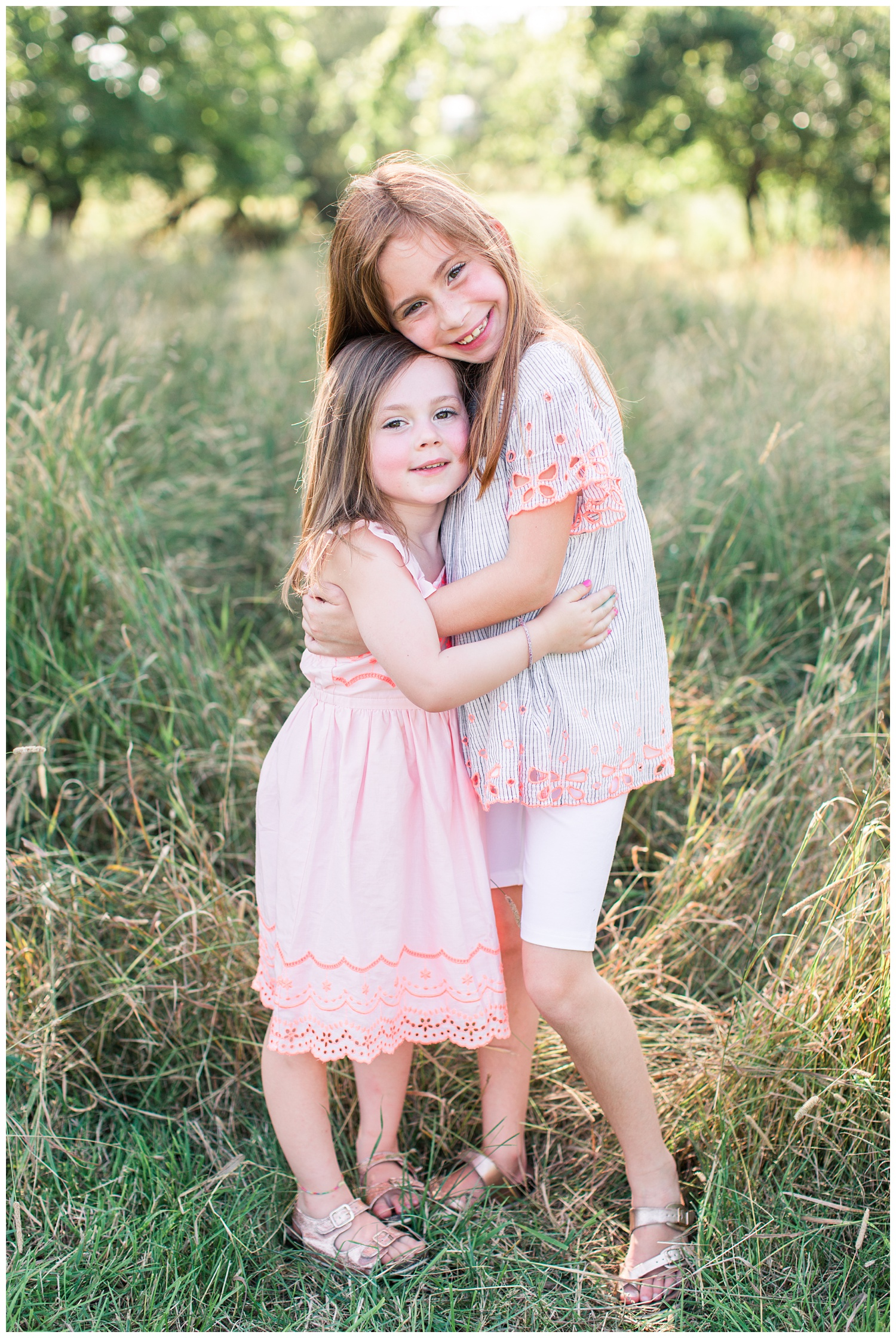 Sisters embrace in a grassy field in Iowa | CB Studio