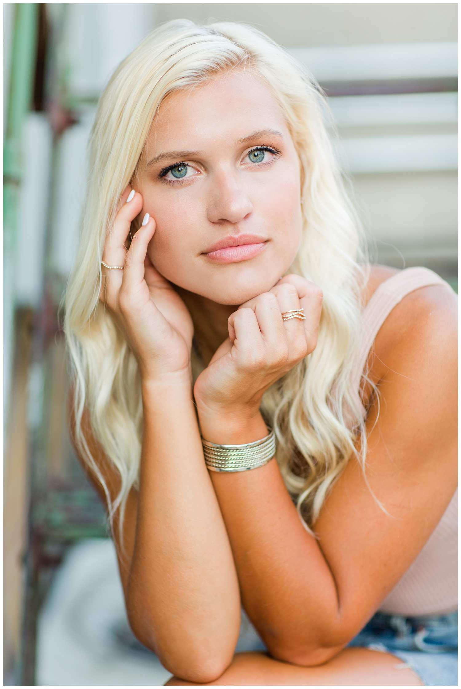 Senior girl cups her hands around her face while siting on a rusty metal staircase in downtown Algona, Iowa | CB Studio
