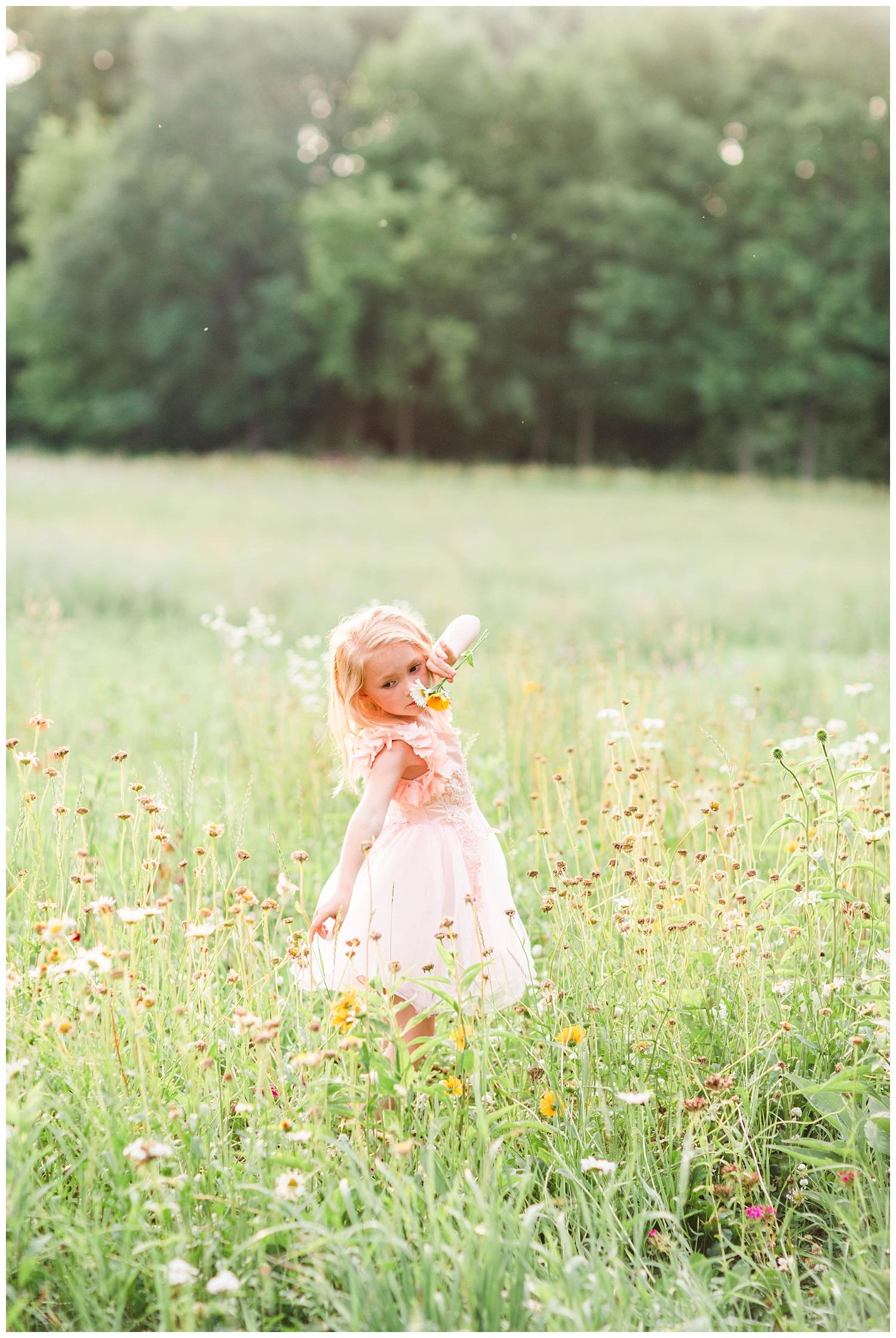 Little Liella dances in a field of wild flowers holding a bouquet wearing tutu du monde couture dress by Trish Scully | CB Studio