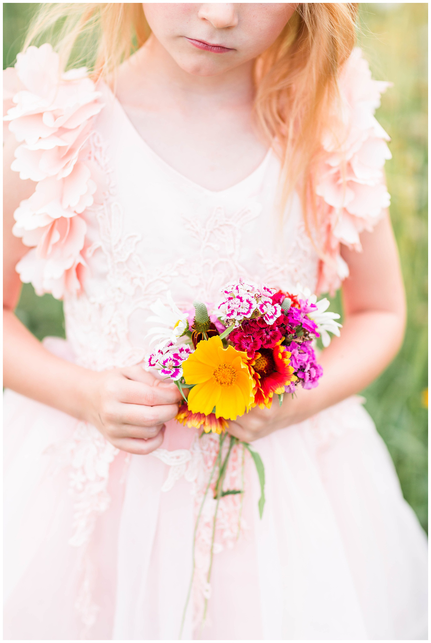 Little Liella stands in a field of wild flowers holding a bouquet wearing tutu du monde couture dress by Trish Scully | CB Studio