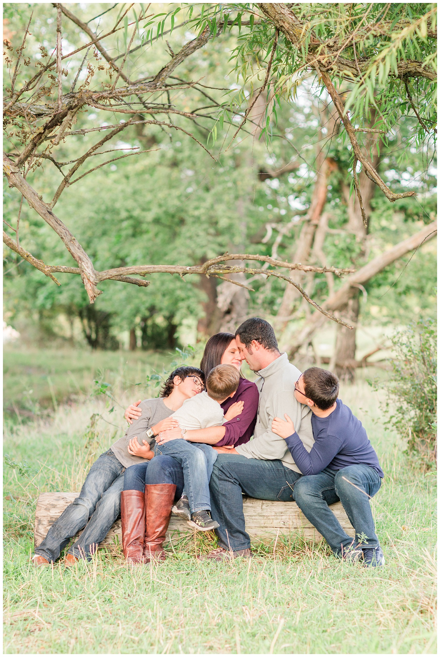 Family snuggles in close while sitting on a log in a pasture in rural Iowa | CB Studio