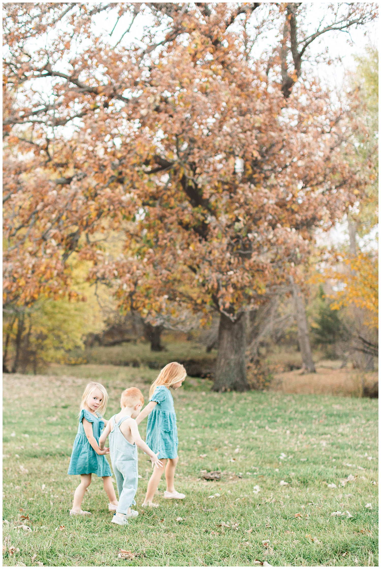 Three children dressed in vintage teal walk holding hands in a grassy pasture | CB Studio