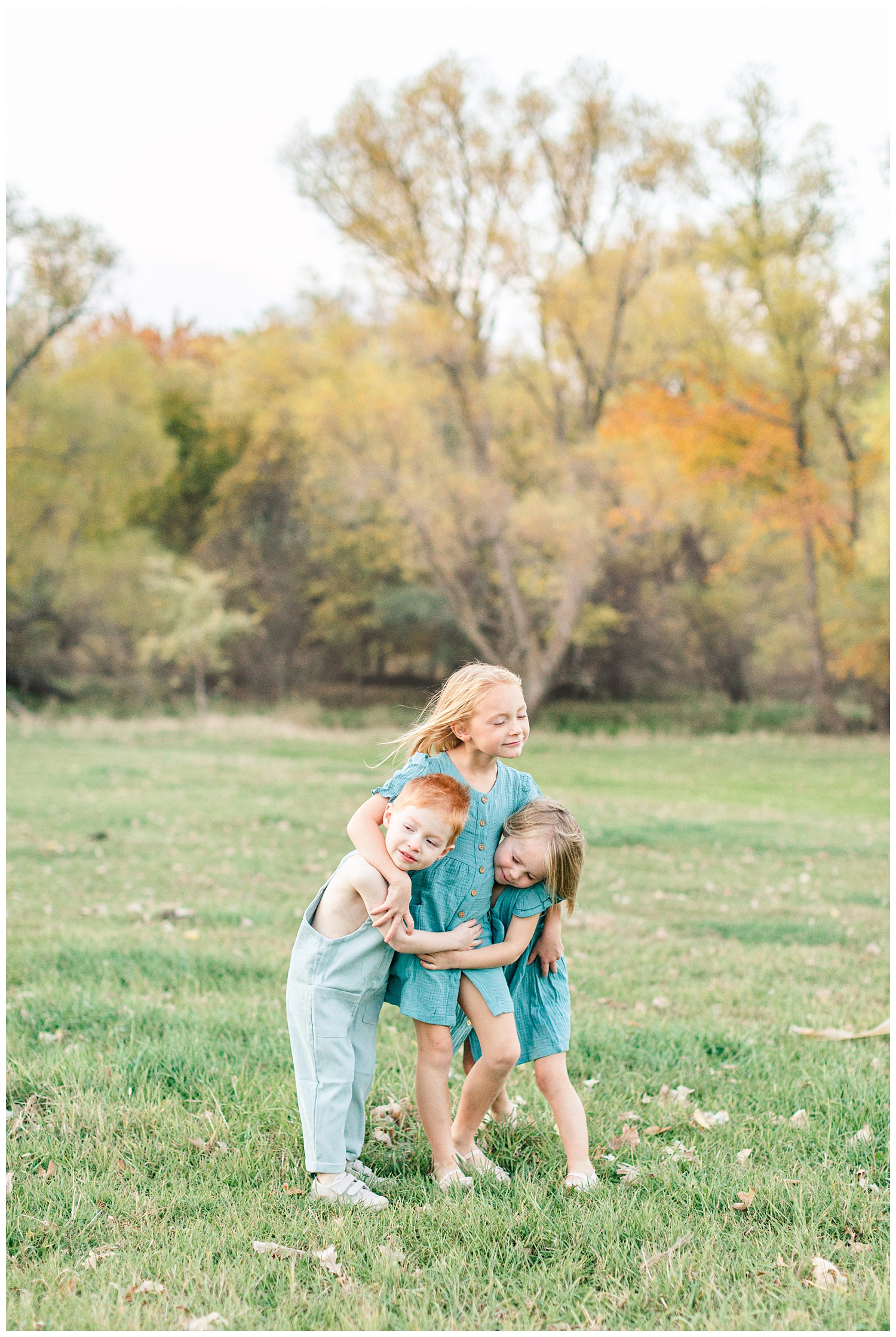 Three children dressed in vintage teal embrace each other in a grassy field looking onward | CB Studio