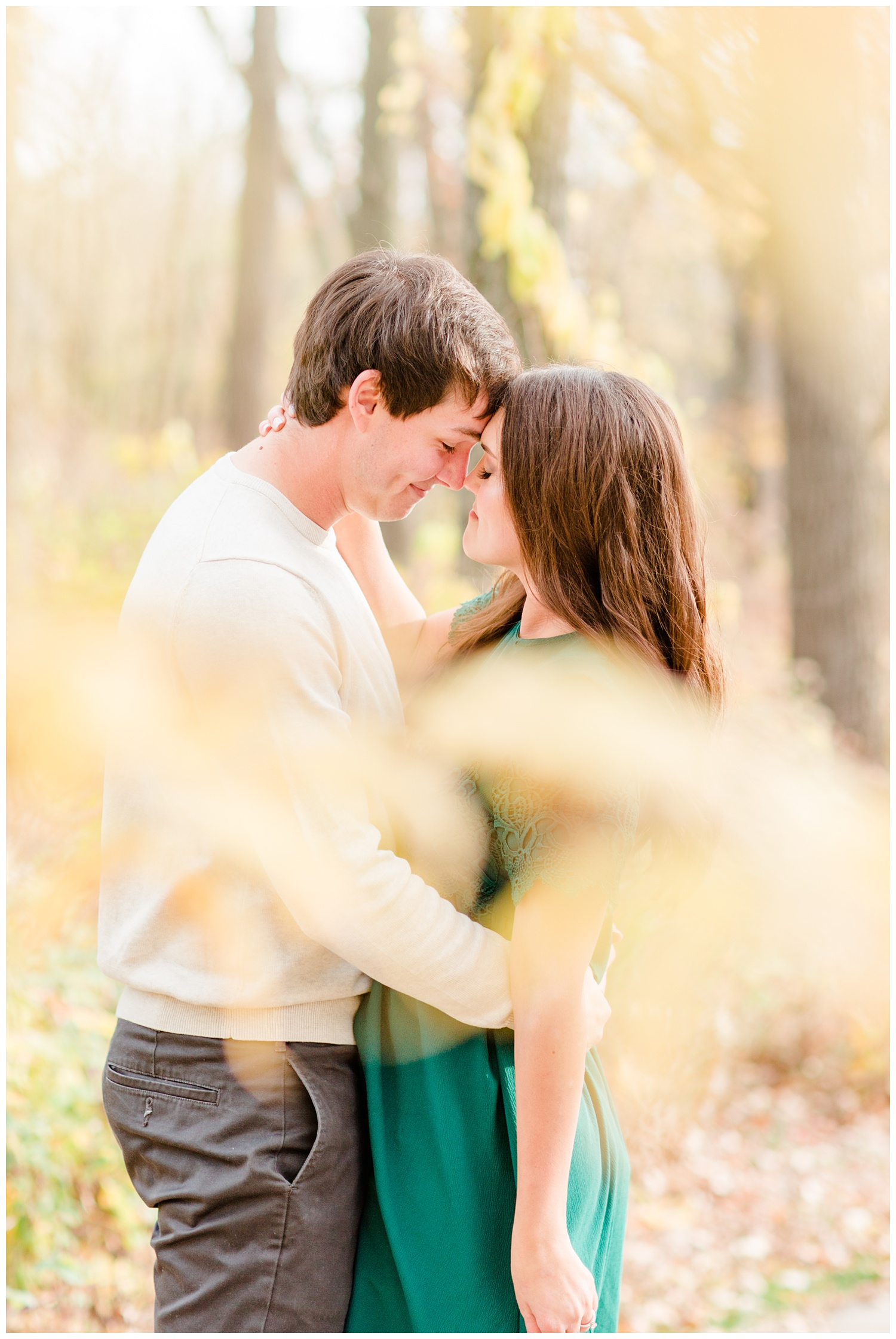 Fall in Iowa, Jenna wearing an emerald green dress embraces Brady in the middle of an autumn path at Lost Island Nature Center   CB Studio