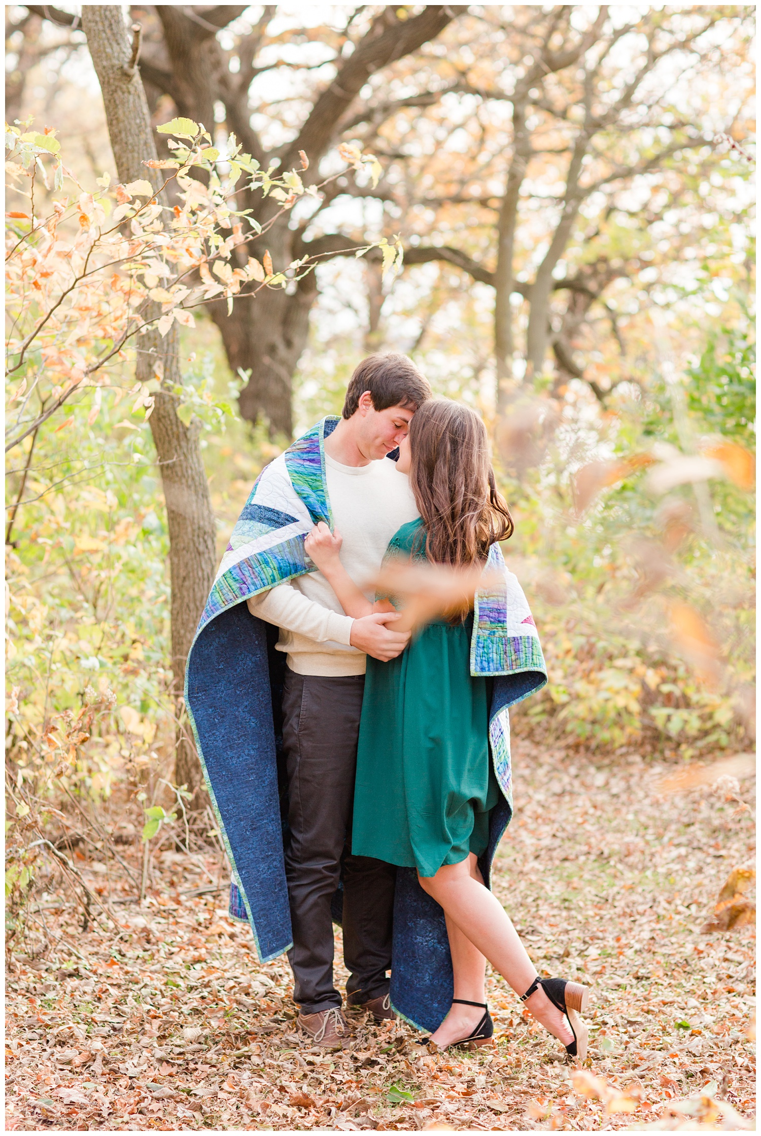Fall in Iowa, Jenna wearing an emerald green dress embraces Brady while both wrapped in a quilt in the middle of an autumn path at Lost Island Nature Center   CB Studio