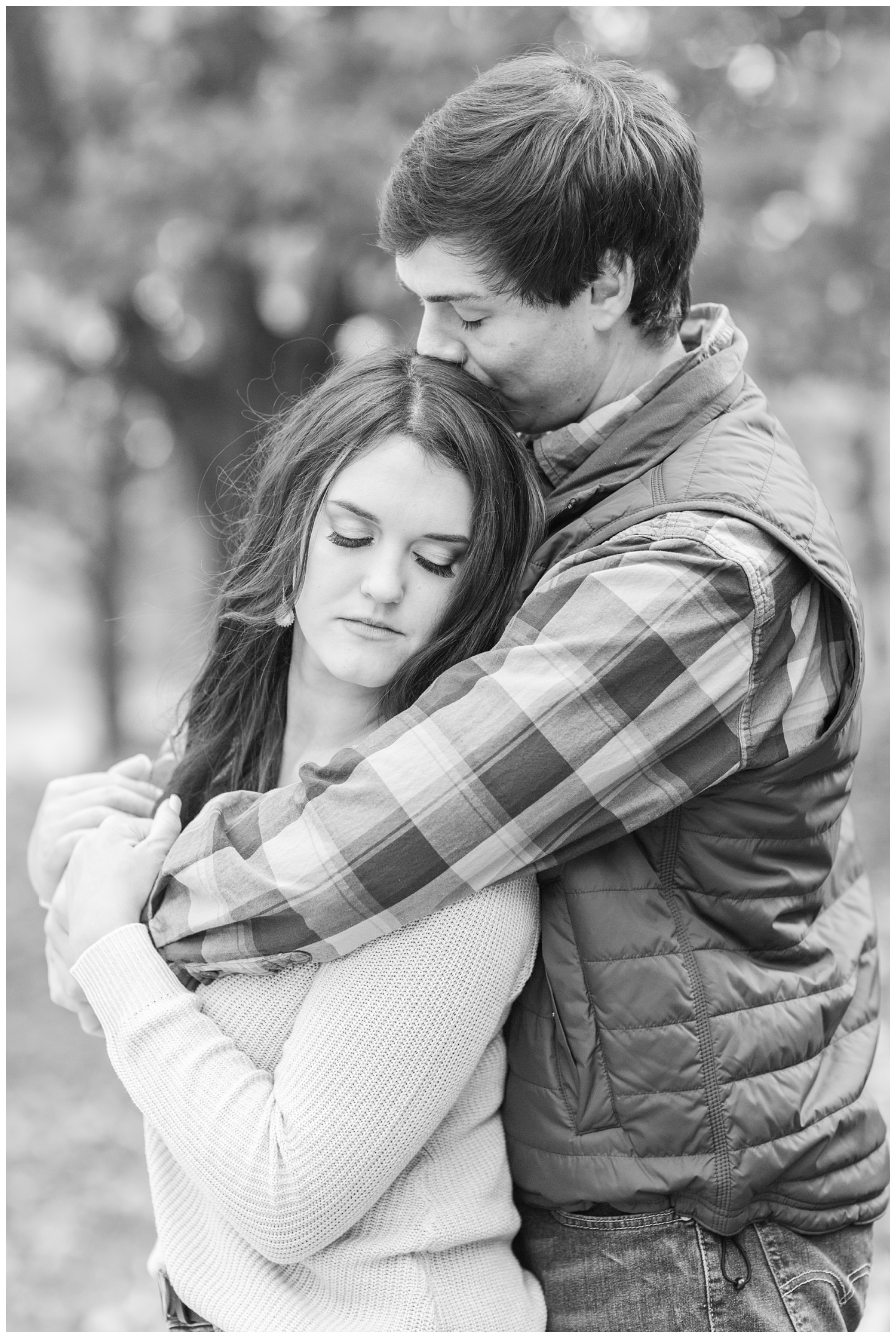 Fall in Iowa, Brady embraces Jenna and kisses her head in the middle of an autumn path at Lost Island Nature Center   CB Studio