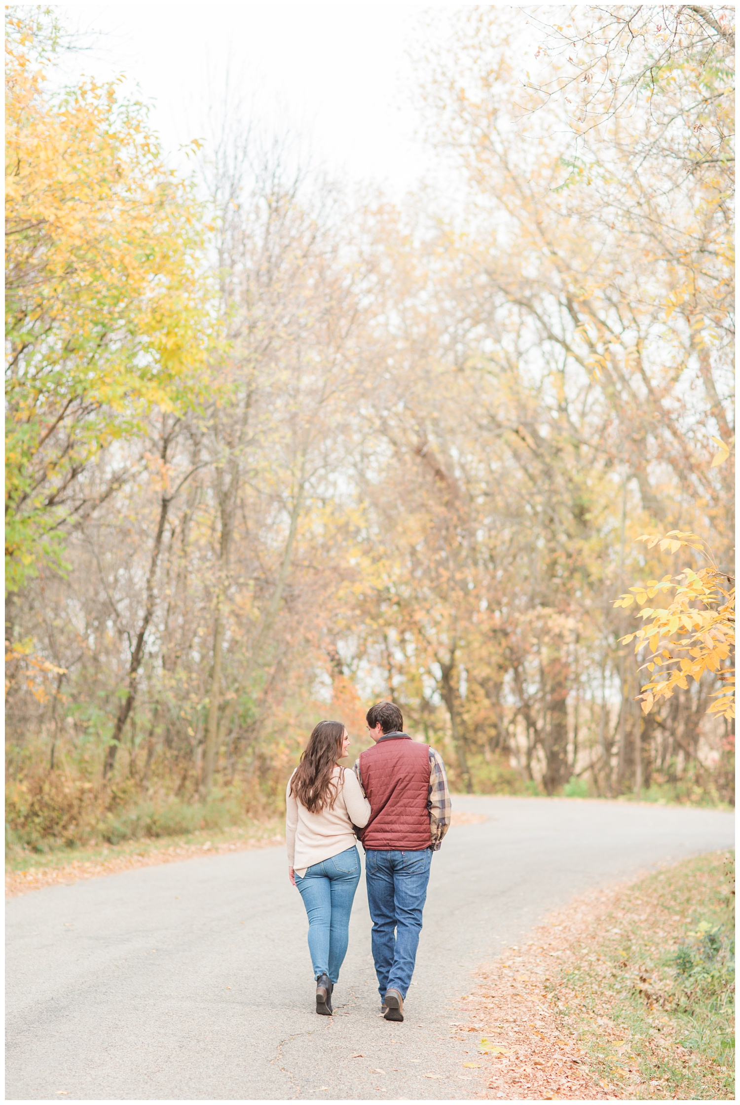 Fall in Iowa, Jenna and Brady link arms as they walk along an autumn path at Lost Island Nature Center   CB Studio