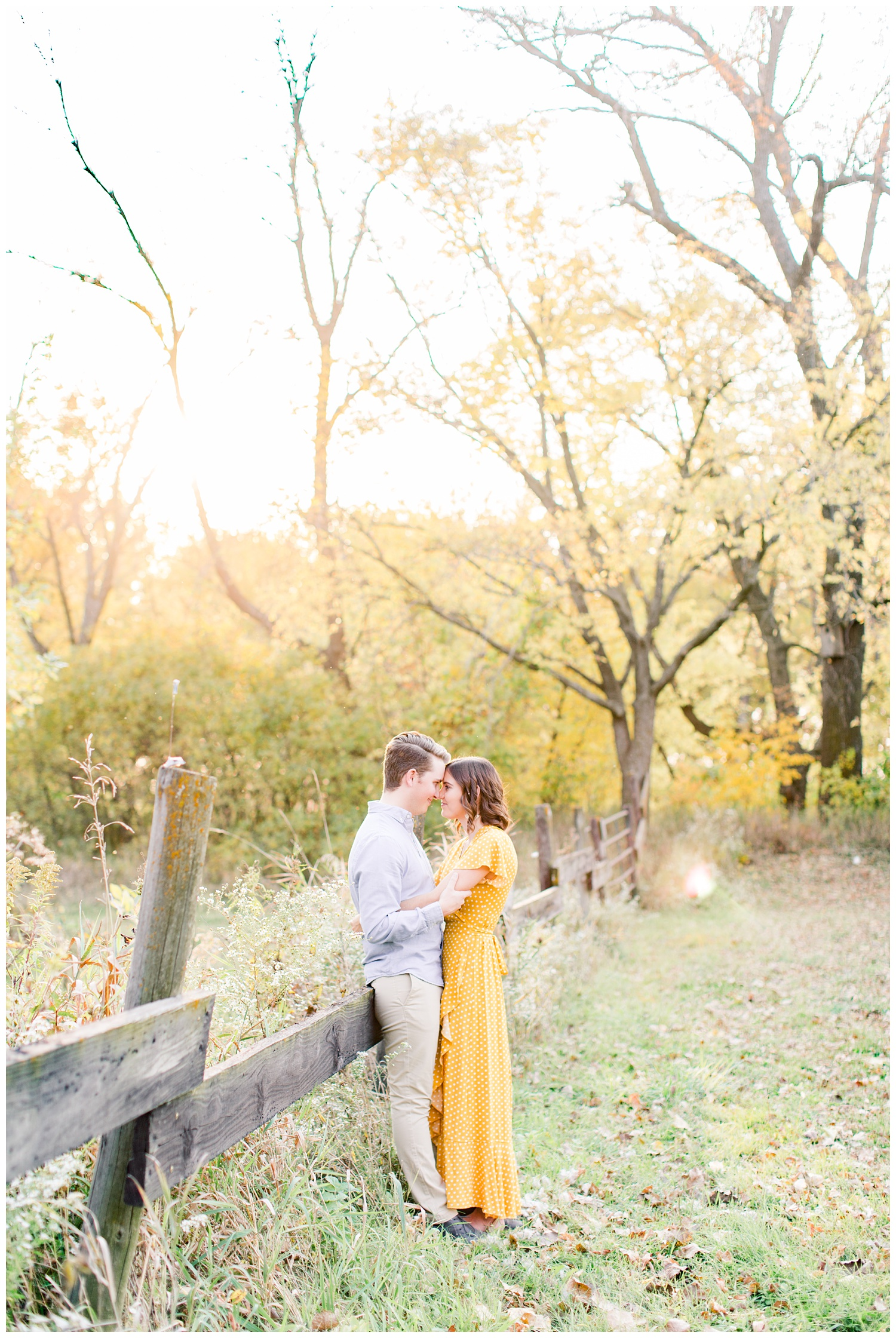 Jadi and Luke lean against a wooden fence post in a grassy field in Iowa during the fall for engagement photos | CB Studio