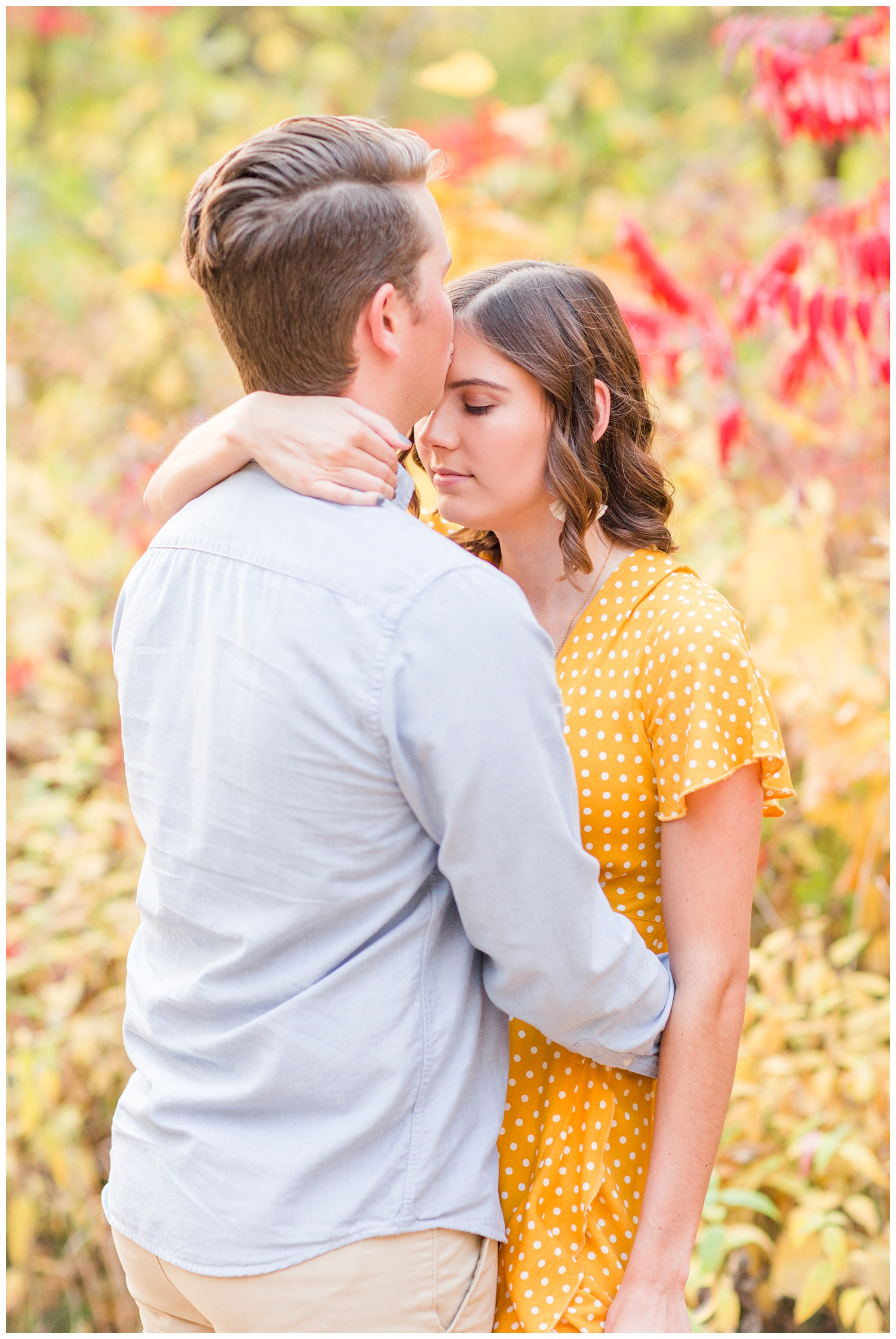 Jadi wearing a yellow flowing dress looks down as Luke kisses her forehead while embracing together in a grassy field in Iowa during the fall for engagement photos | CB Studio