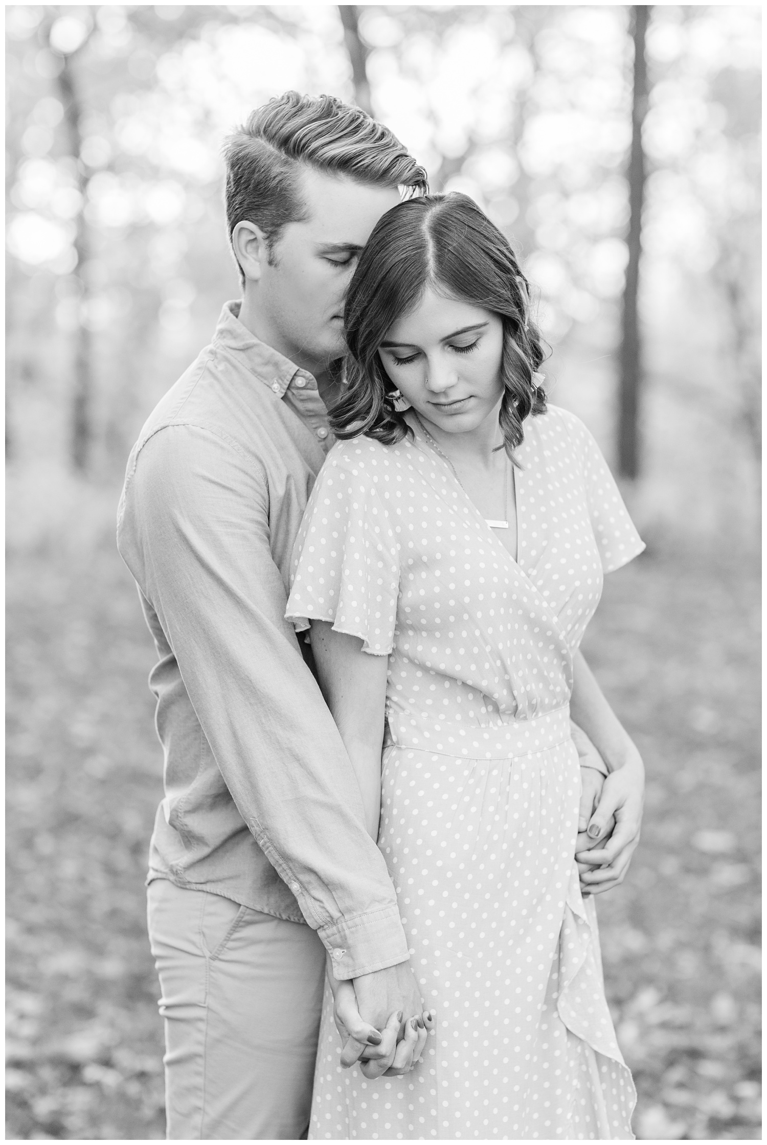 Jadi wearing a yellow flowing dress lovingly looks down as Luke whispers into her ear while embracing together in a grassy field in Iowa during the fall for engagement photos | CB Studio