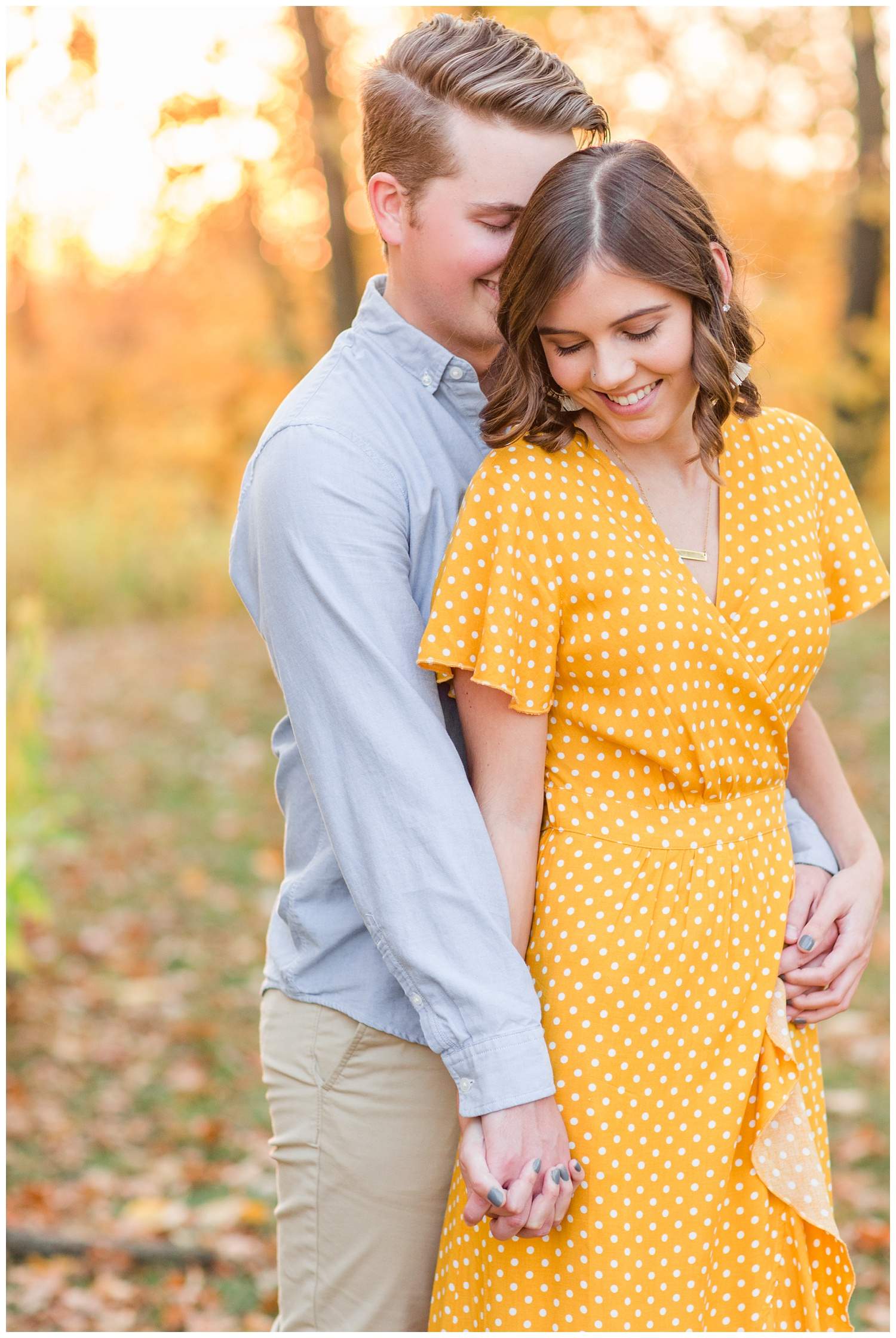 Jadi wearing a yellow flowing dress smiles as Luke whispers into her ear while embracing together in a grassy field in Iowa during the fall for engagement photos | CB Studio