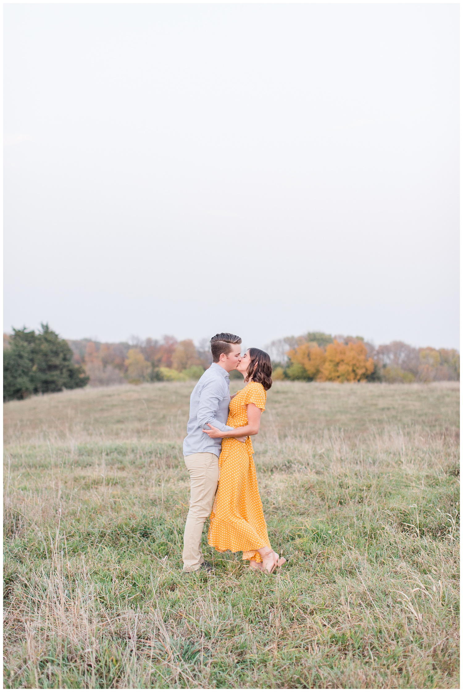 Jadi wearing a yellow flowing dress kisses Luke while embracing together in a grassy field in Iowa during the fall for engagement photos | CB Studio
