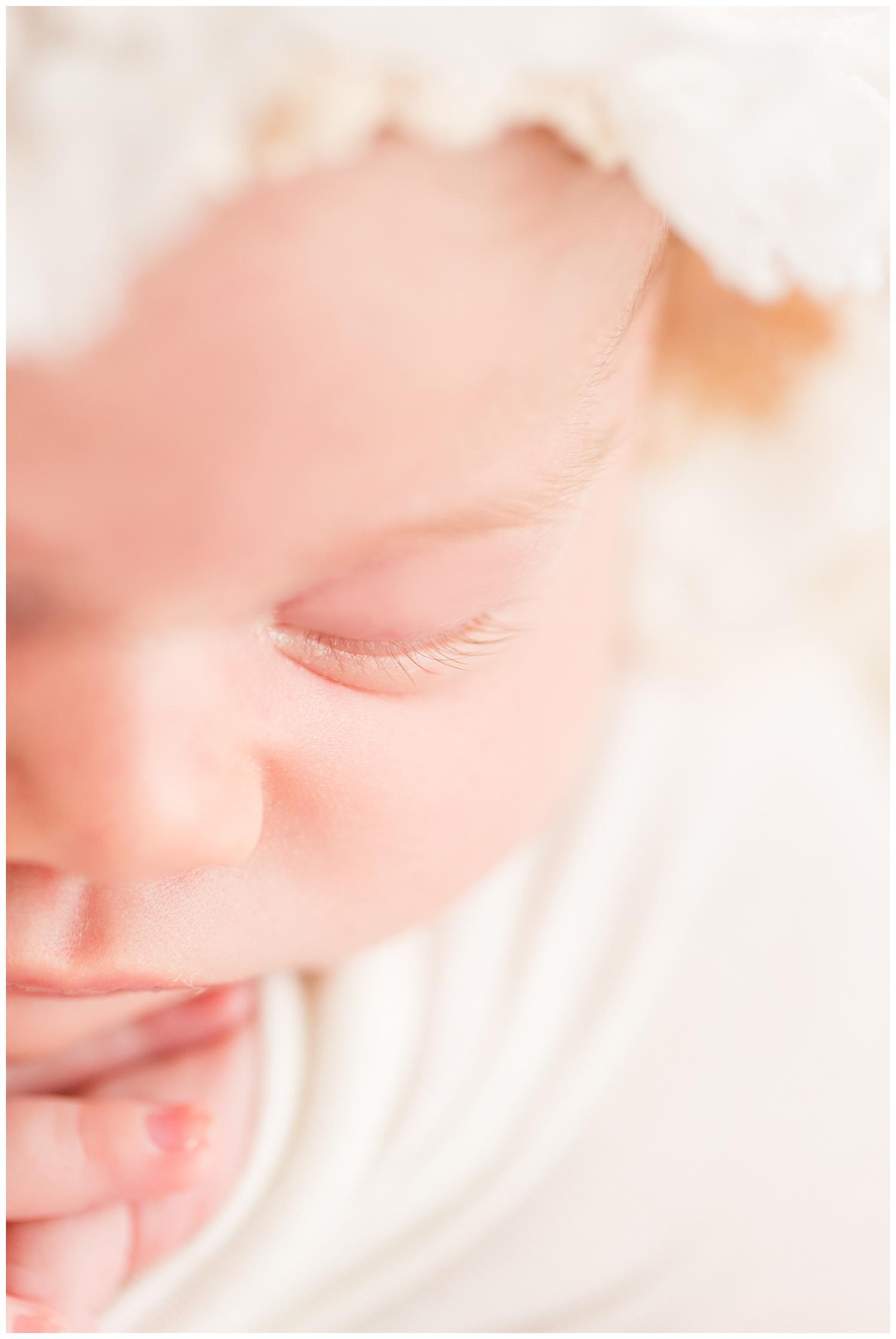 Newborn wearing all white closeup of baby girl's eyelashes   CB Studio