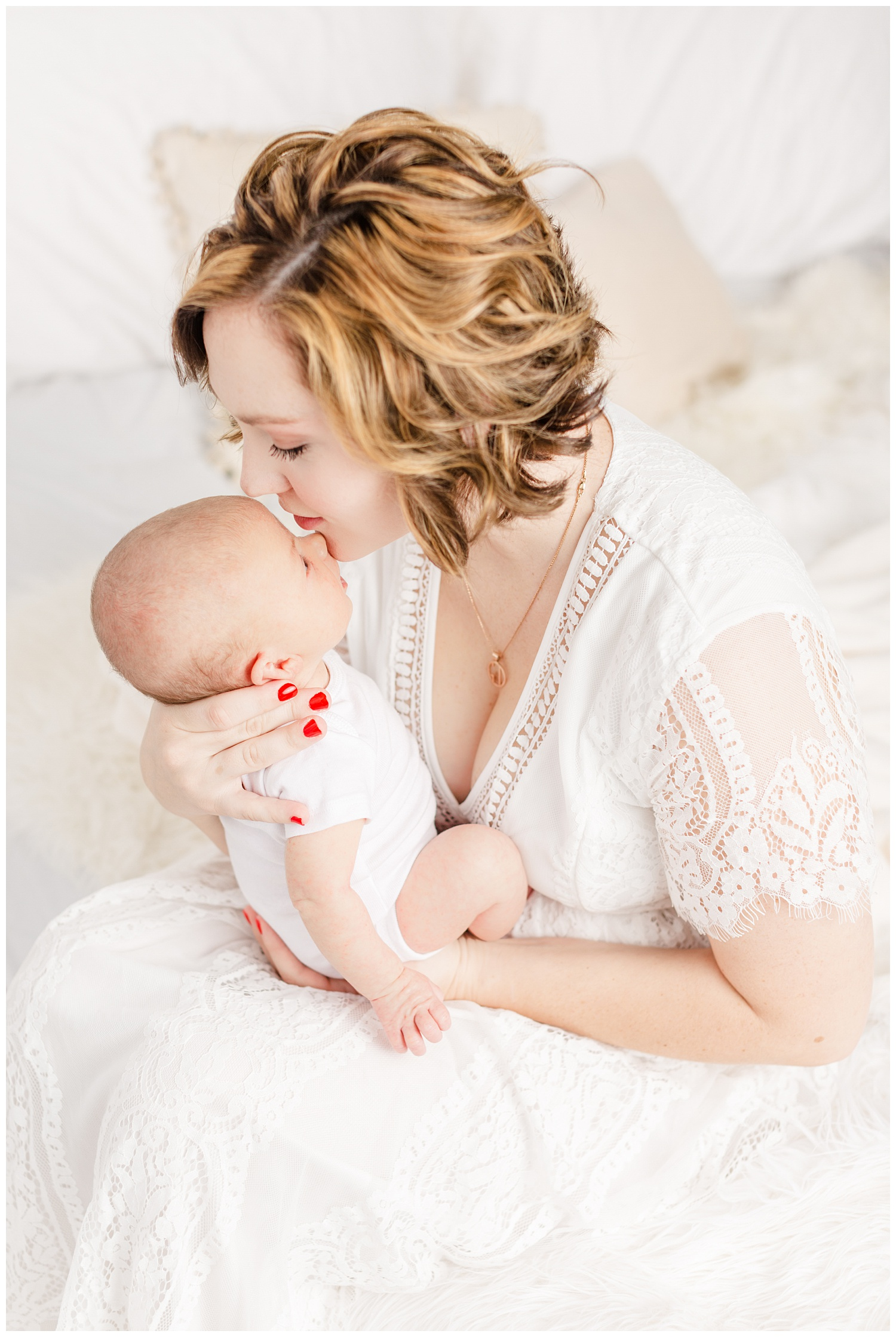 Bree dressed in white lace sits on her bed and gently kisses her new baby boy | CB Studio