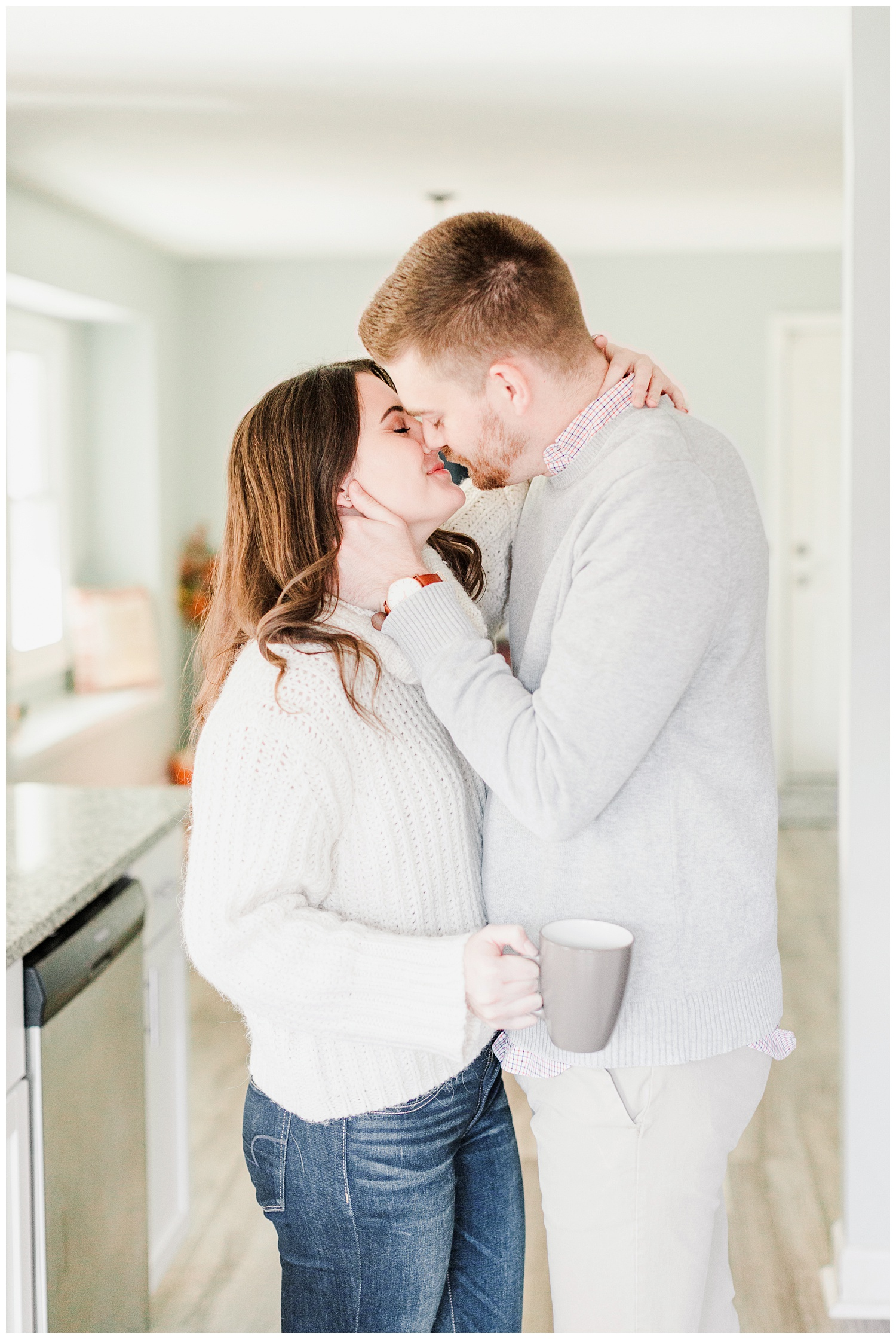 Dustin kisses Jenna while holding a cup of coffee | Cozy Kitchen Engagement Session | CB Studio