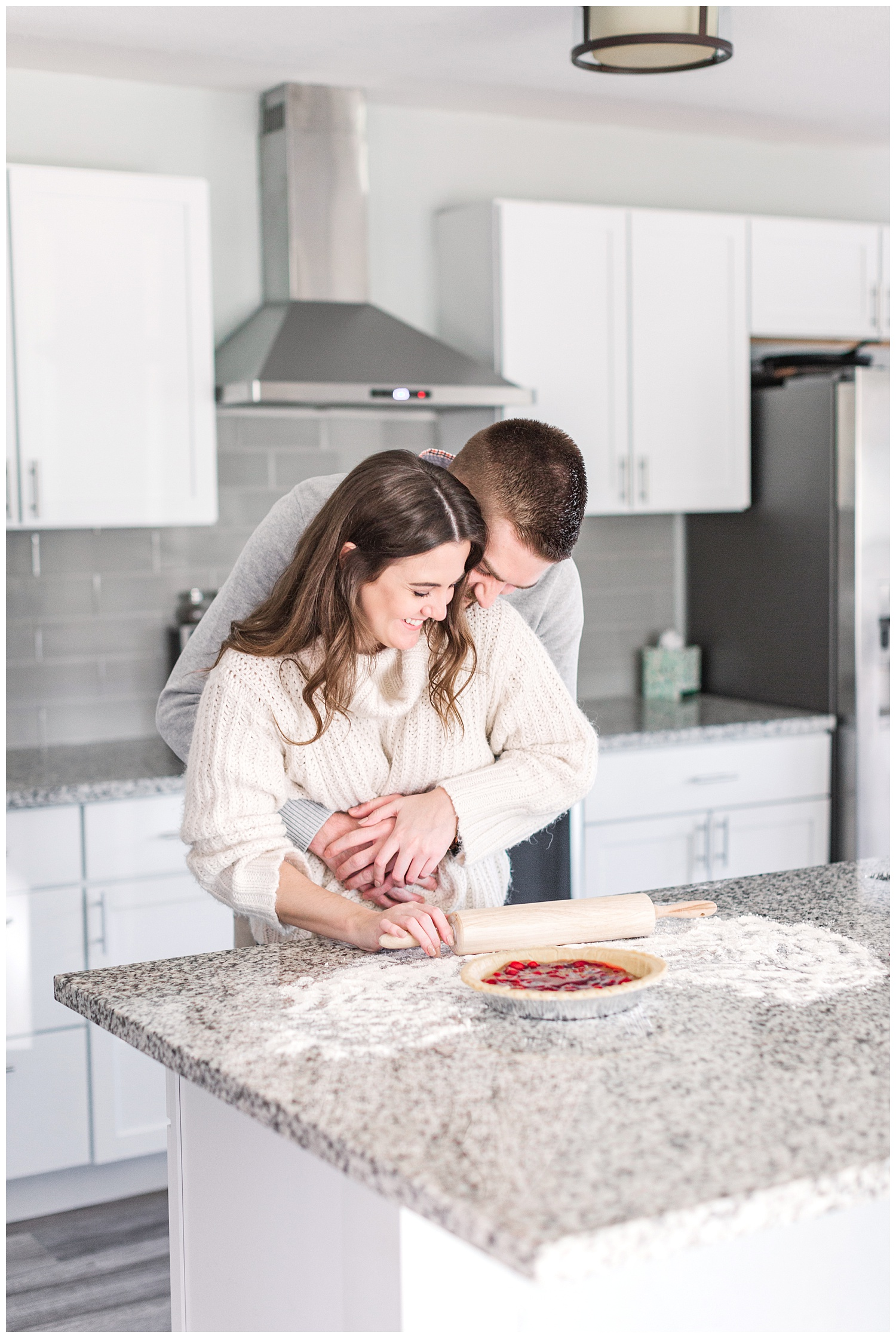 Dustin embraces Jenna from behind while she bakes a cherry pie | Cozy Kitchen Engagement Session | CB Studio