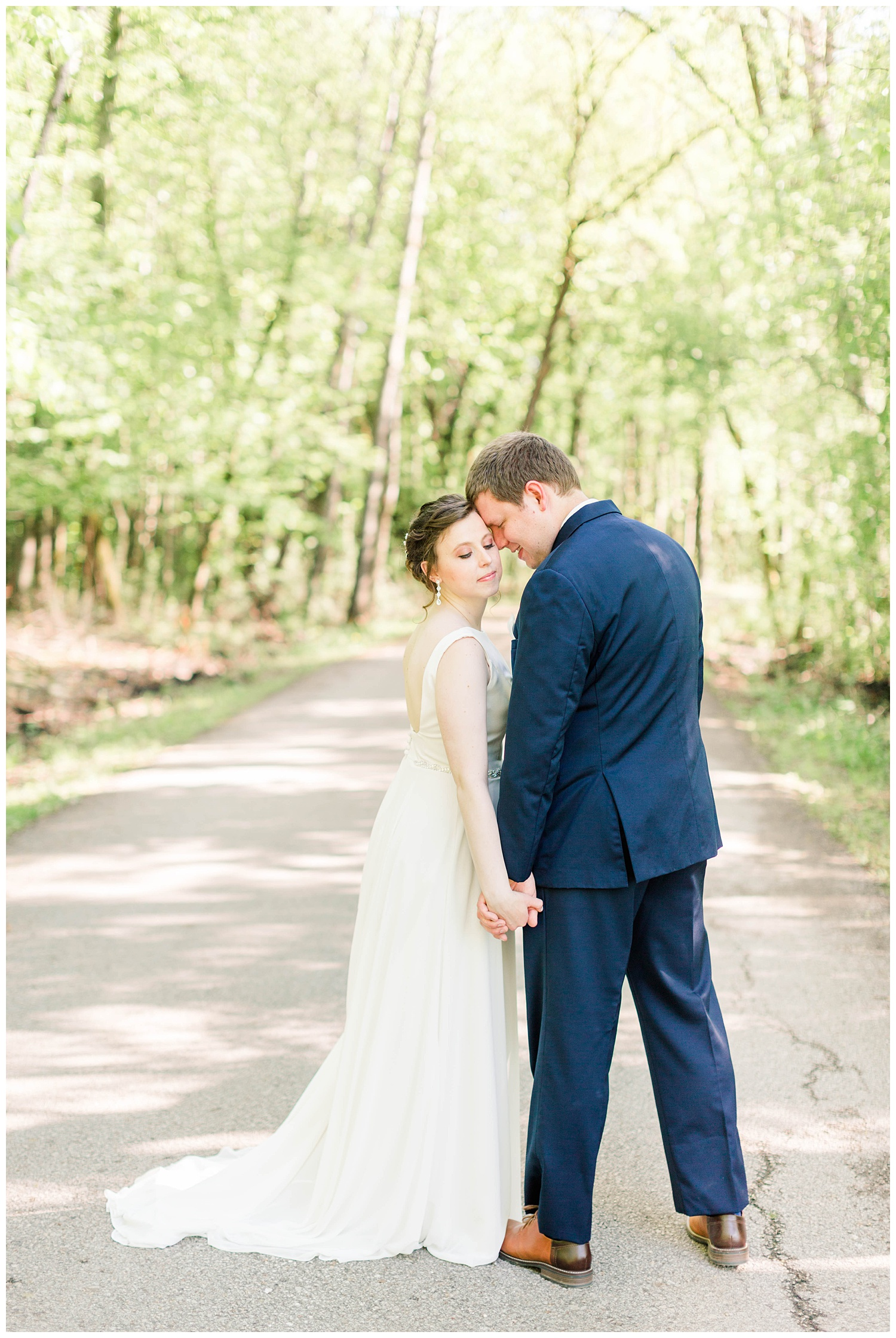 Ryan gently nuzzles his new bride in the middle of a forest pathway | Iowa Wedding Photographer