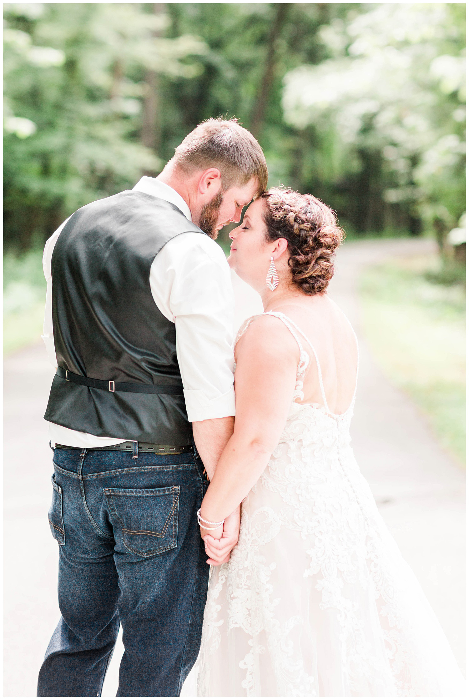 Travis gently nuzzles his new bride in the middle of a forest pathway | Iowa Wedding Photographer