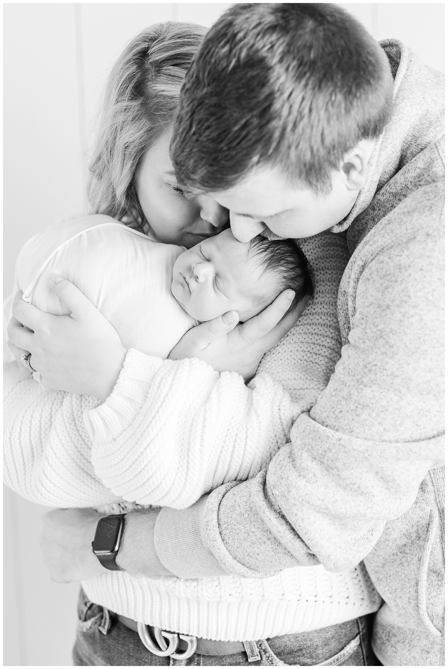 Mom and dad snuggle their newborn baby girl and gently kiss her head. | CB Studio