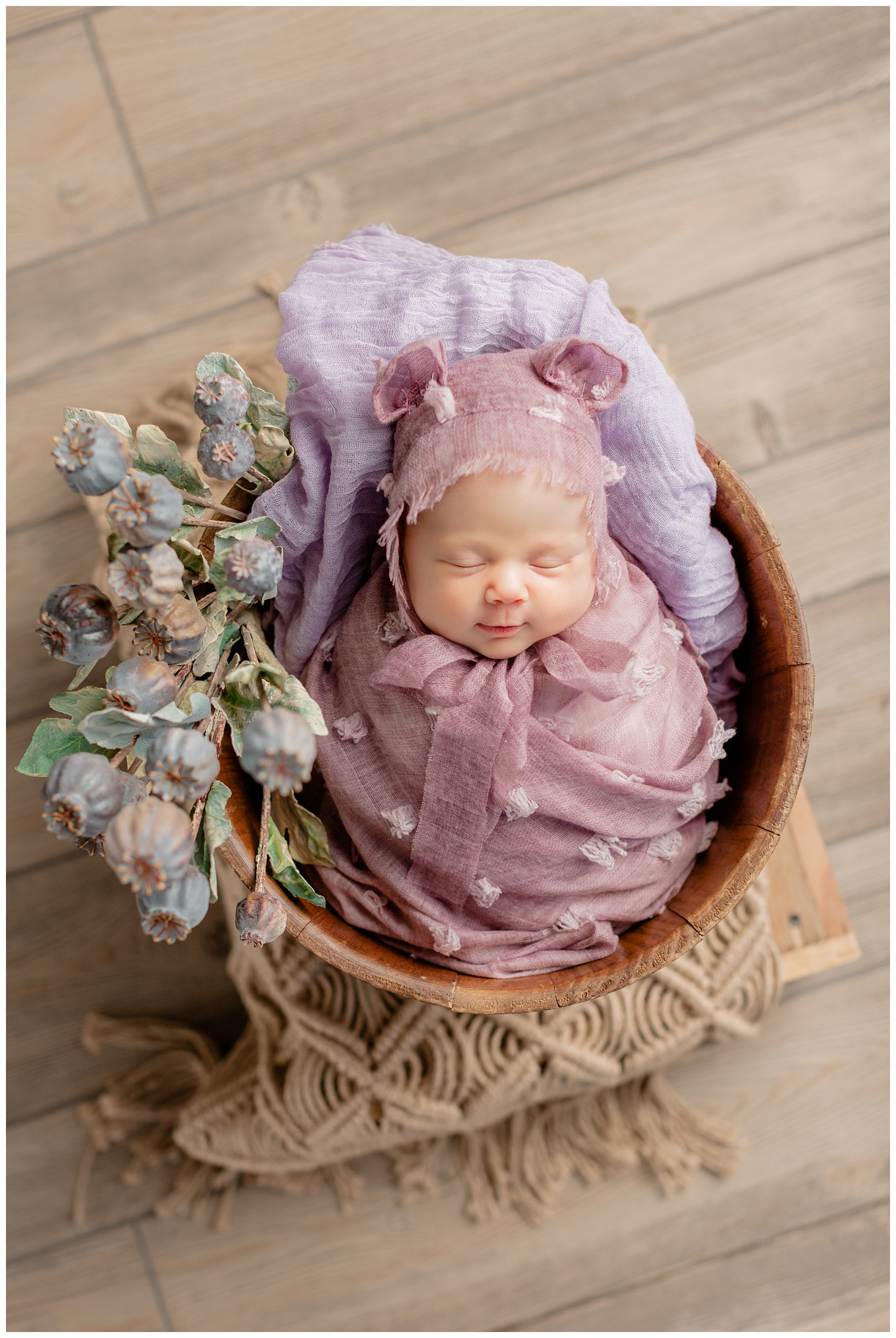 Newborn baby girl Remi swaddled in a mauve textured wrap and bear ear bonnet lying in a basket full of flowers | CB Studio
