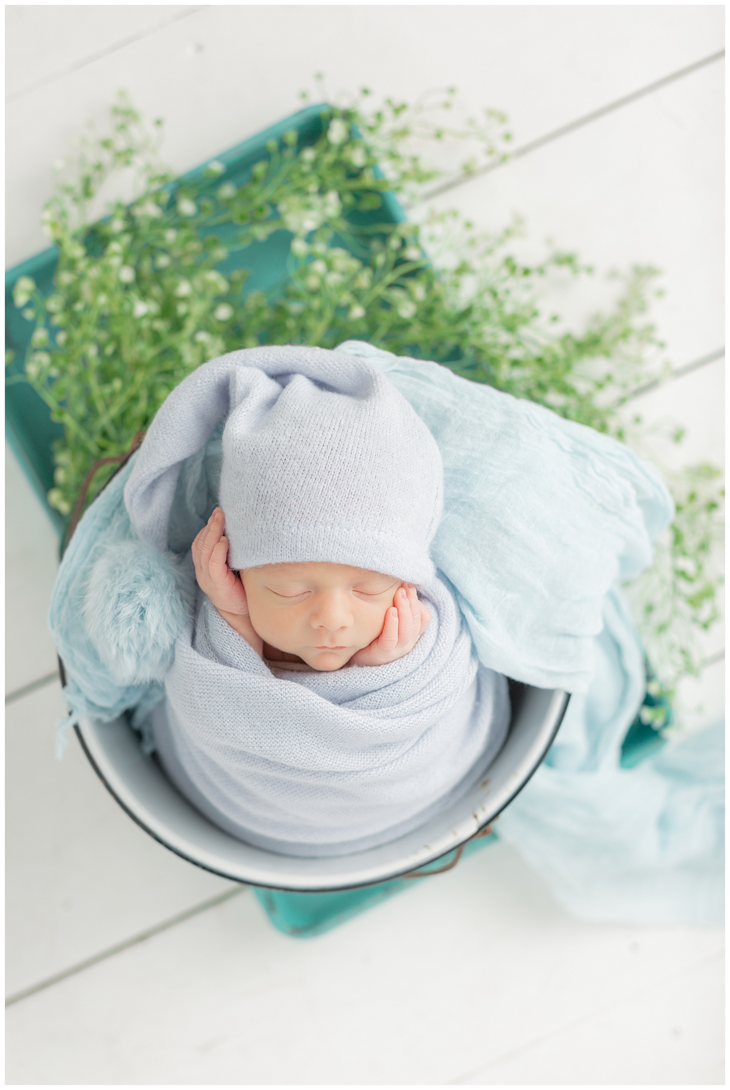 Baby boy Hayes lays in a bucket surrounded with greenery while swaddled in a soft knit blue wrap and night cap | CB Studio