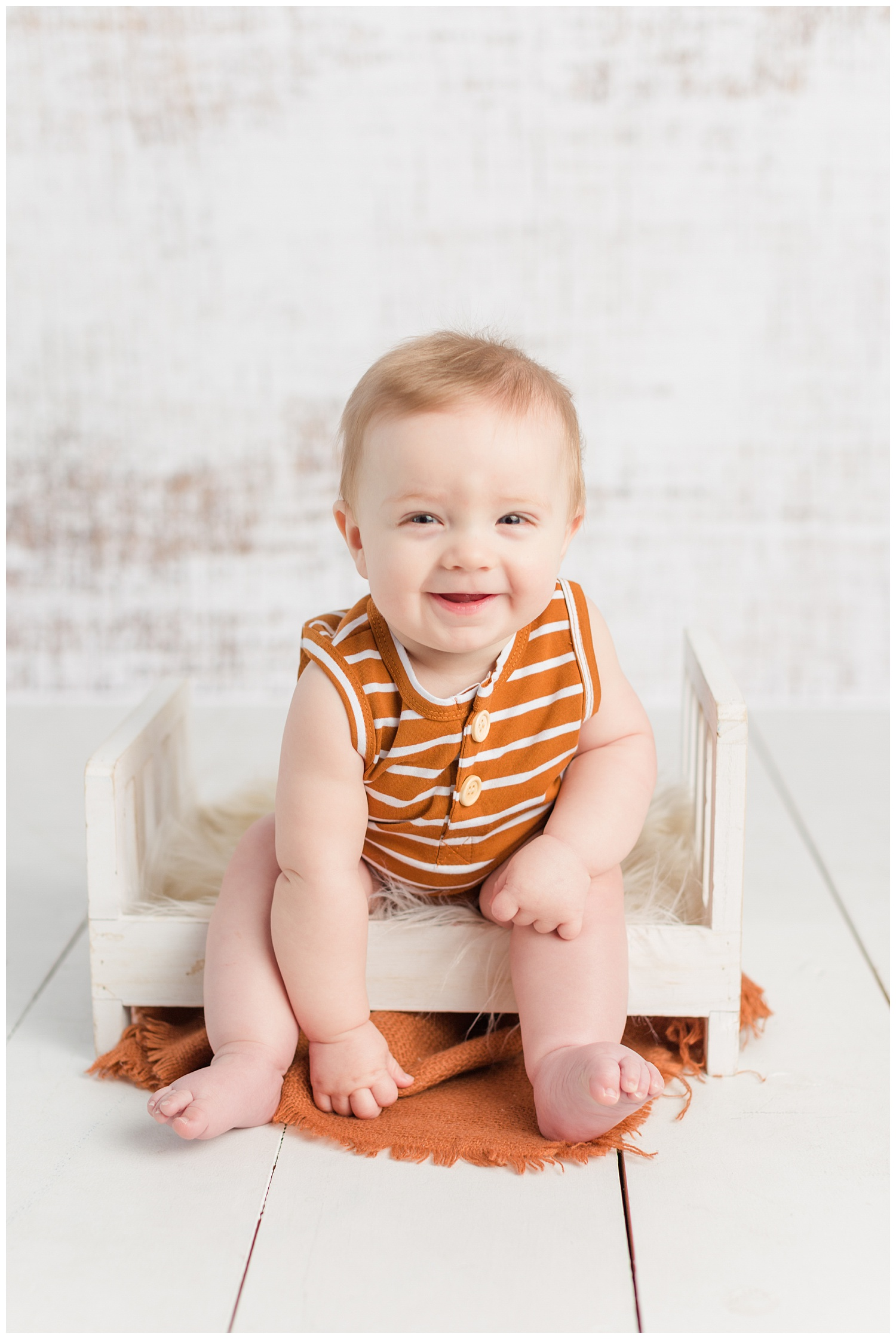 Baby Jackson sitting on a little white bed wearing a camel colored romper | CB Studio