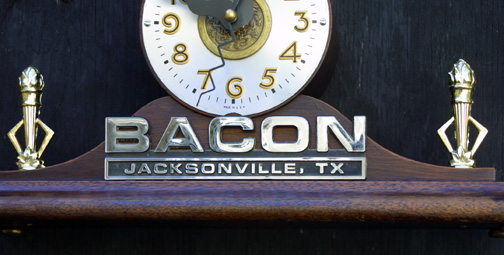 """""""Porcus Fugit"""" Clock by Jason Burnett wood, found objects, prize hog trophy figure, car dealer emblem, trophy torches, Chinese coin/token and other objects 9.25"""" x 12"""" x 4.5"""" $600 #11880"""