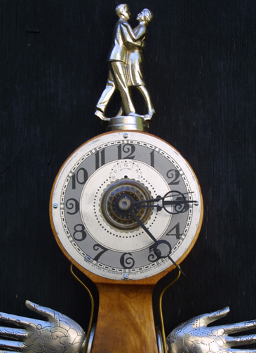 """Lover"" wall clock by Jason Burnett wood, found objects: Dance trophy figure, placecard holders, auto medallion, Chevrolet emblem letters, salvaged Herman Miller banjo clock body 17.5"" x 9"" x 3"" $700 #11883"