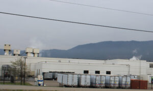 An image of the outside of a Bush Brothers factory. Shipping truck loads are in front of the factory and mountains lay in the background.