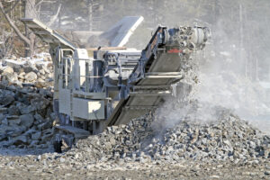 A generalized image of a rock crusher as it crushes large chunks of rock into smaller pieces