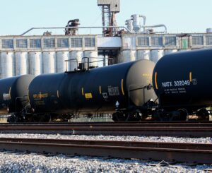 Tank Rail Cars on a track with industrial buildings in the background on a clear day. This is an example image of the type of confined space the employees may have dealt with.