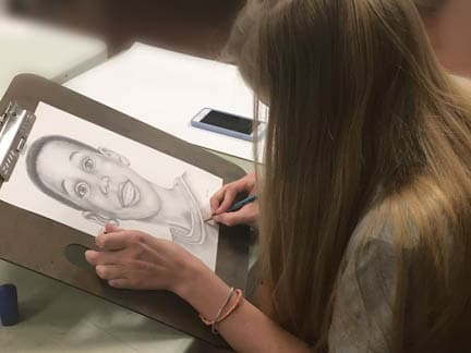 Teenager drawing a portrait in anrt class.